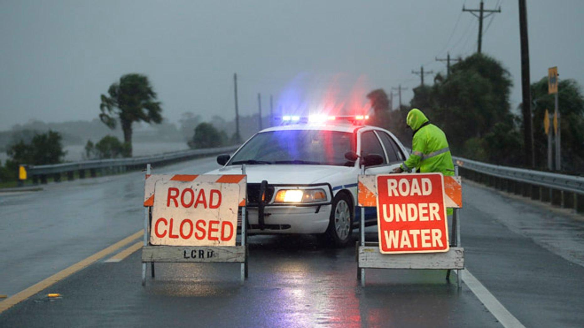 Police block the road entering Cedar Key, Fla., as Hurricane Hermine nears the Florida coast, Thursday, Sept. 1, 2016.