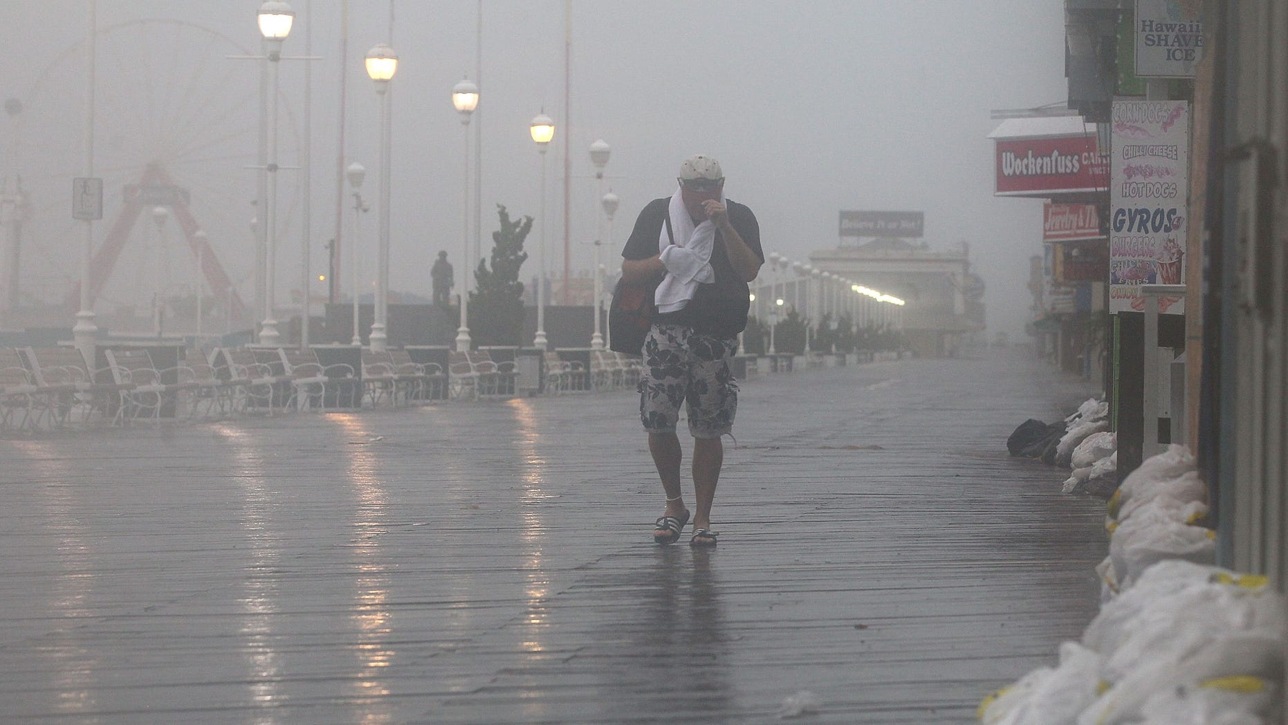 OCEAN CITY, MD - AUGUST 27: A man walks down the board walk as winds from approaching Hurricane Irene start hit the area on August 27, 2011 in Ocean City, Maryland. The state of Maryland has declared a state of emergency as heavy winds and surf from Hurricane Irene approaches the coast.  (Photo by Mark Wilson/Getty Images)