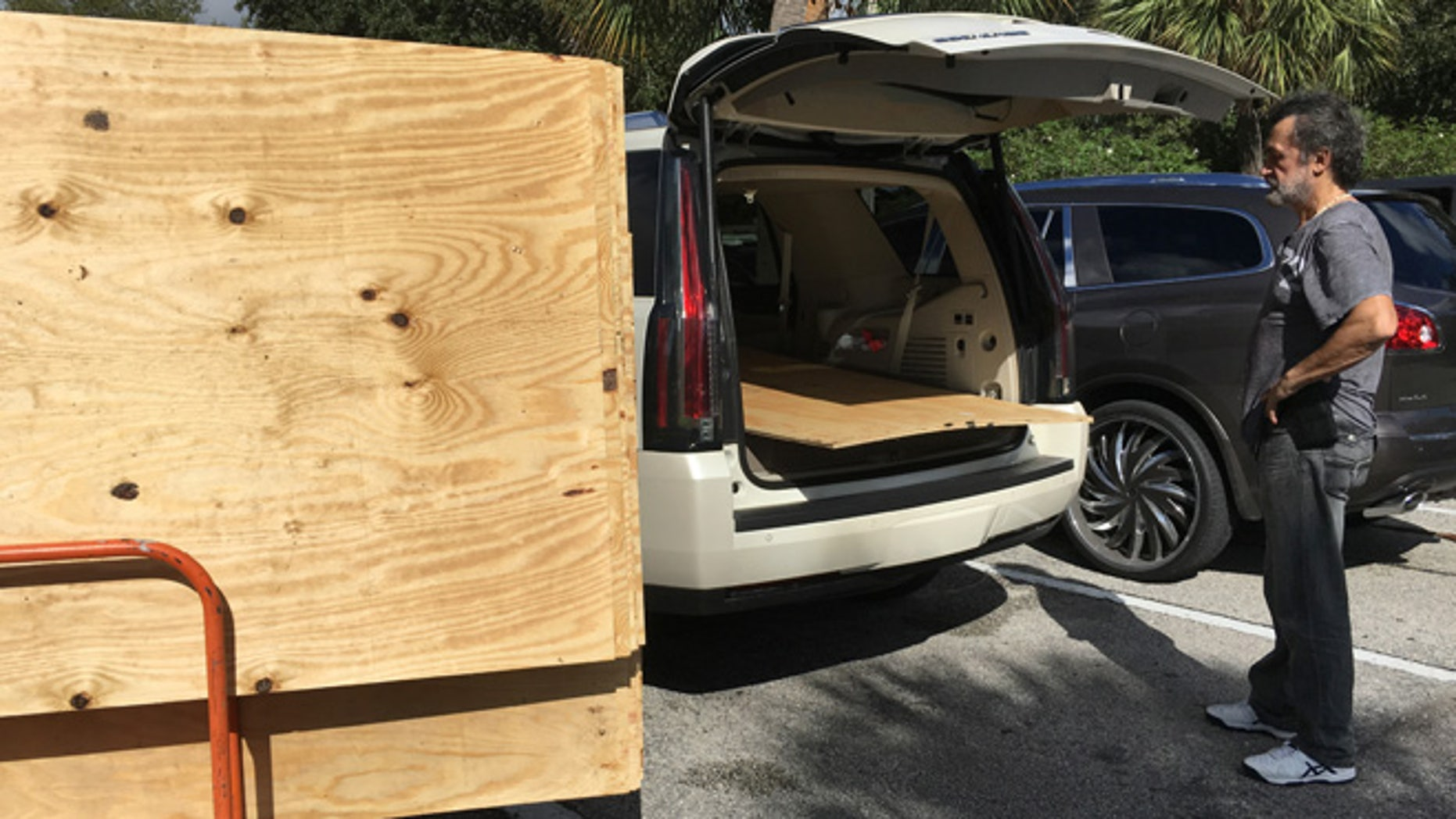 Danny Delarocca, of Boca Raton, loads plywood onto his brother's car at the Home Depot in Deerfield Beach, Fla. Tuesday, Oct. 4, 2016.