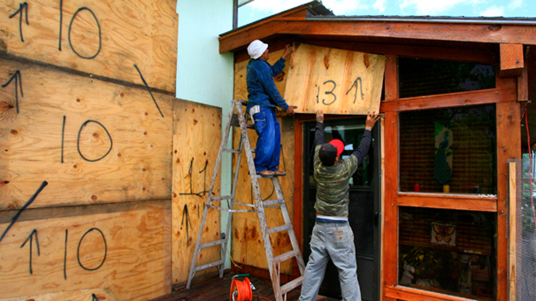 June 29: Norecio Salazar and Leonardo Salinas place a sheet of designated plywood over a window on Jim and JoAnne Farber's home on the Delta Lake Reservoir in preparation for Tropical Storm Alex. (AP)