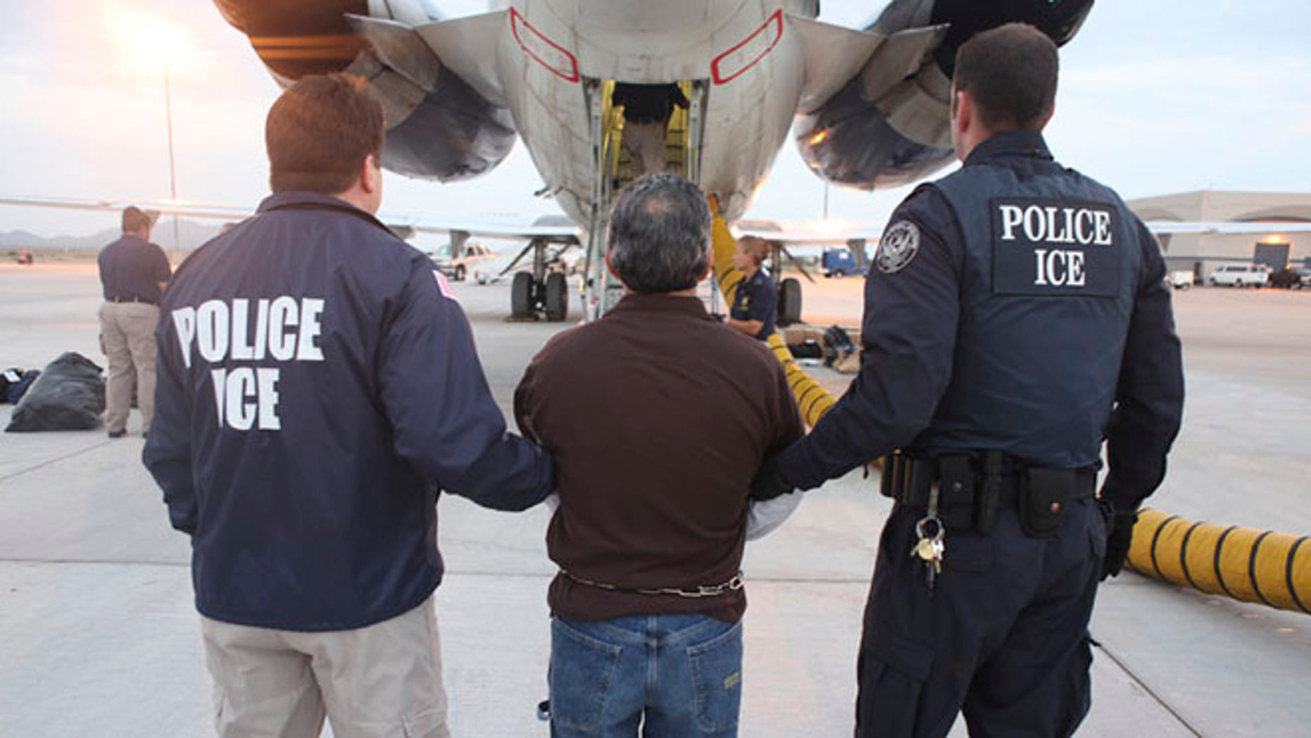 In this July 12, 2011 file photo, an illegal immigrant is transferred to an awaiting plane bound for Guatemala by U.S. Immigration and Customs Enforcement (ICE) officials in Mesa, Ariz.