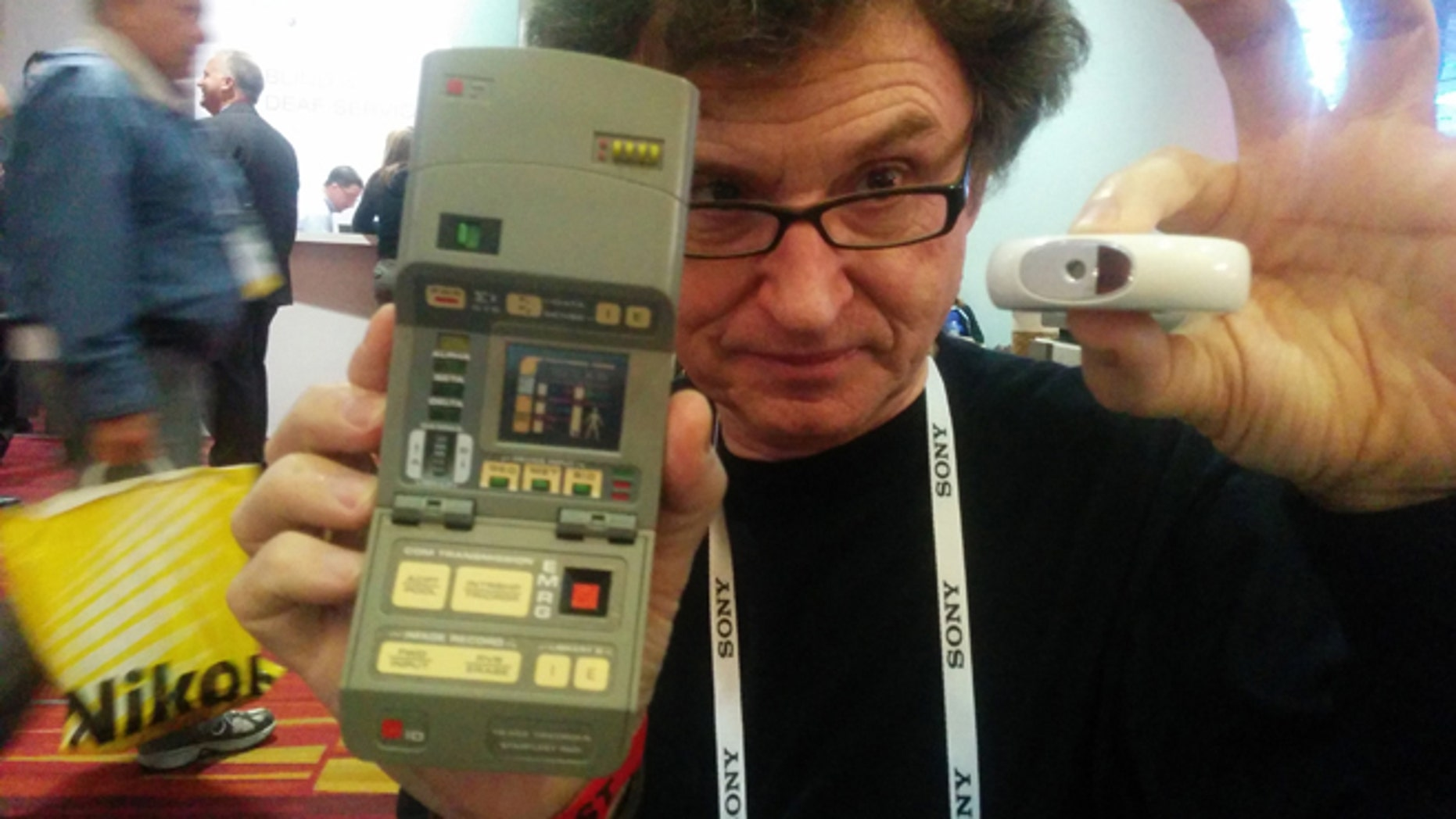 """In Walter De Brouwer's right hand, the tricorder used on the TV series """"Star Trek."""" In his left hand, a real-world version he has invented."""
