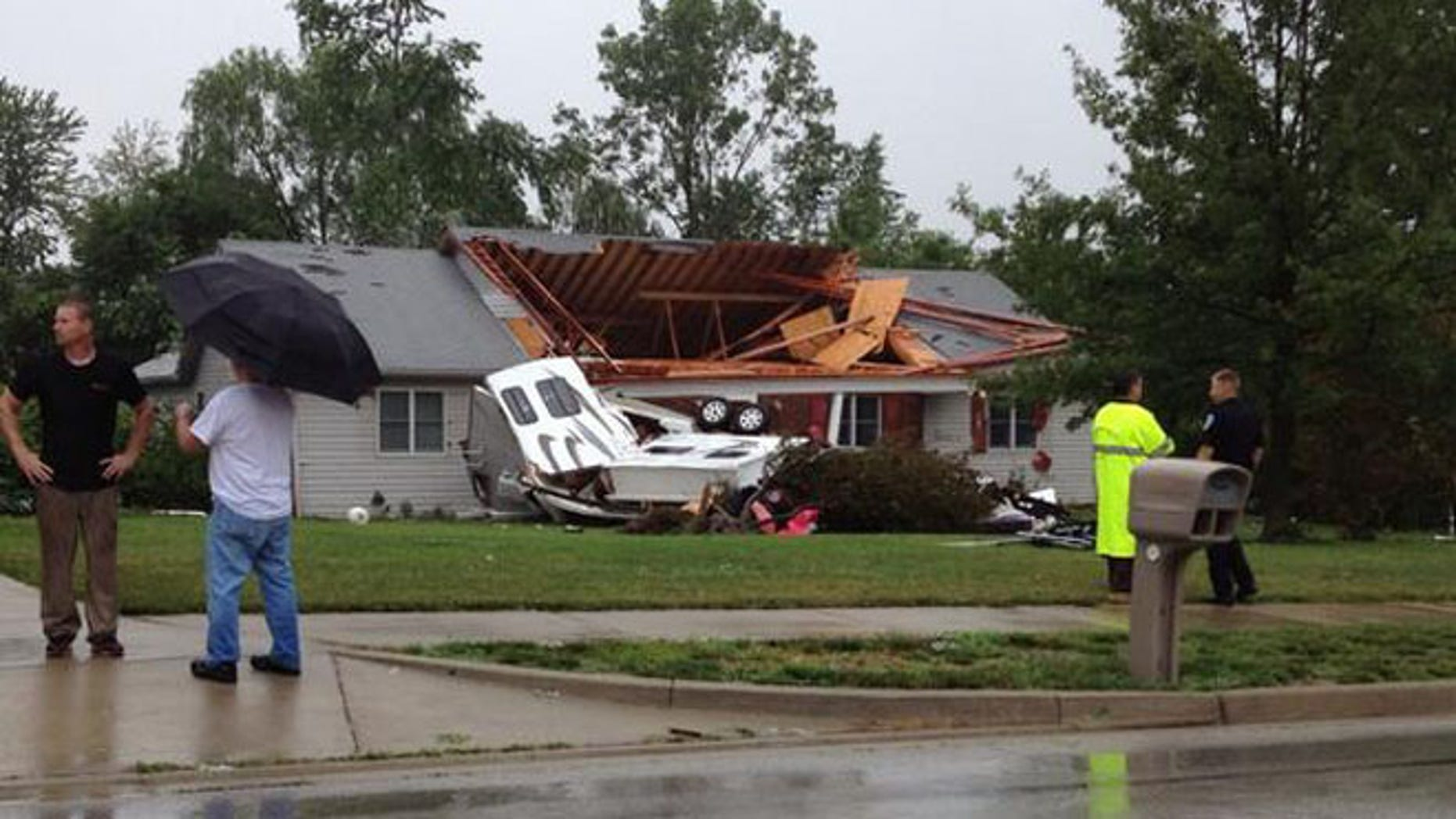 June 24, 2014: Residents stand outside a home that was badly damaged by a tornado in Plainfield, Indiana.