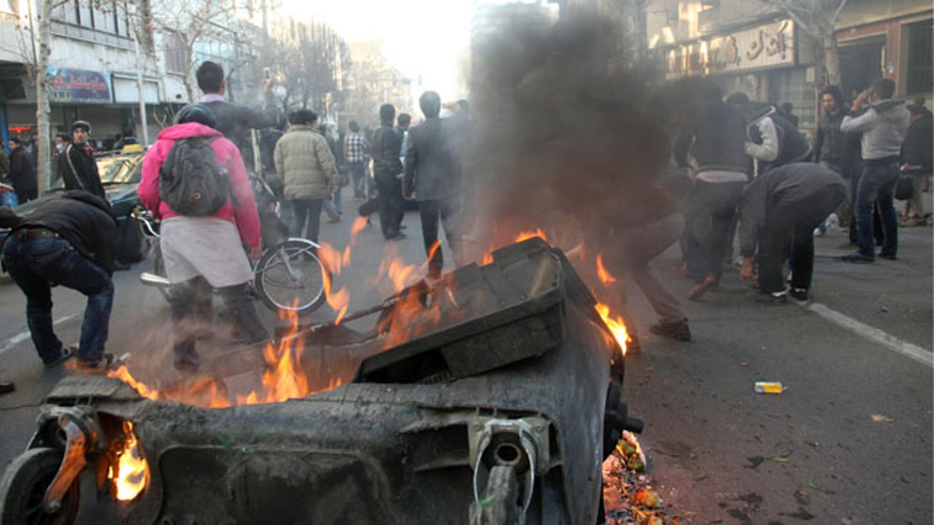 Feb. 14, 2011: This photo shows Iranian protestors attending an anti-government protest as a garbage can is set on fire, in Tehran, Iran.