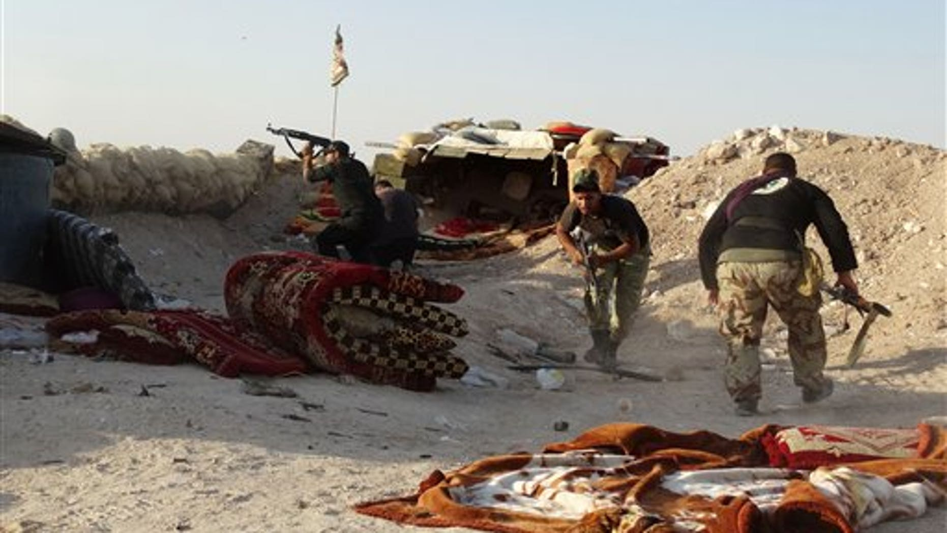 In this photo taken Monday, June 15, 2015, Iraqi security forces defend their positions against an Islamic State attack in Husaybah, 5 miles east of Ramadi, Iraq. (AP Photo)
