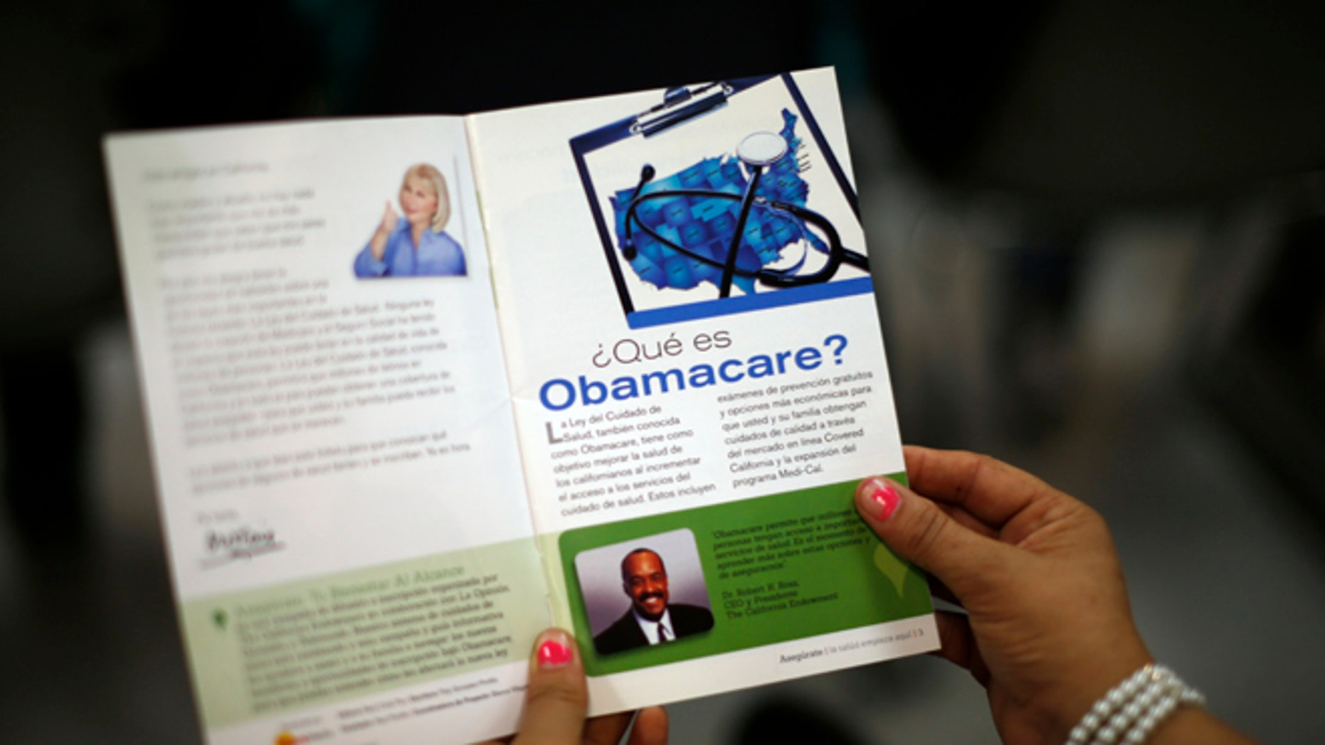 FILE: March 27, 2014: A woman reads a pamphlet in Spanish at a health insurance enrollment event in Cudahy, Calif.