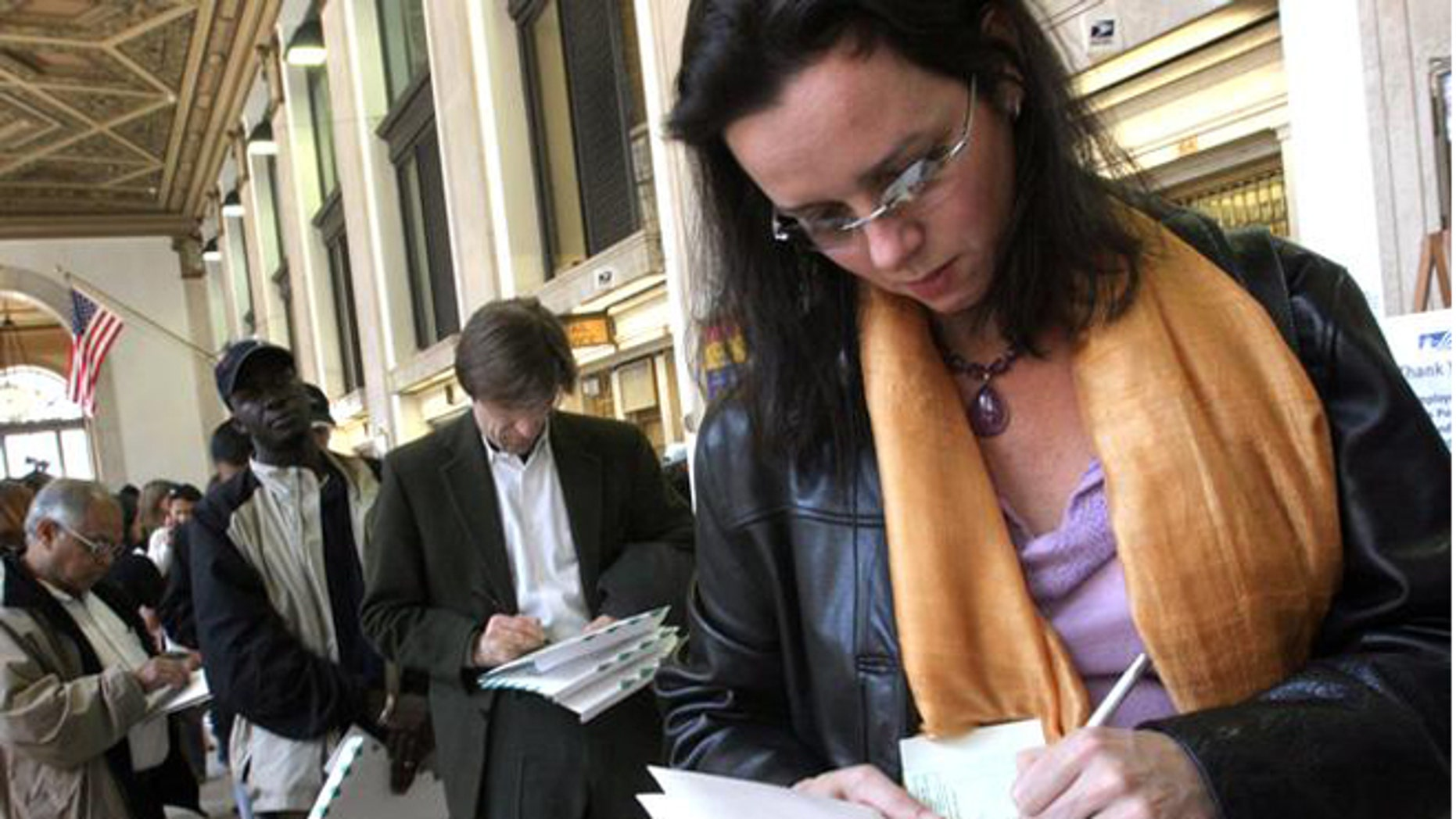 FILE: April 15, 2005: Tax filers fill out a form for certified mail at the General Post Office in New York before sending in her tax returns.