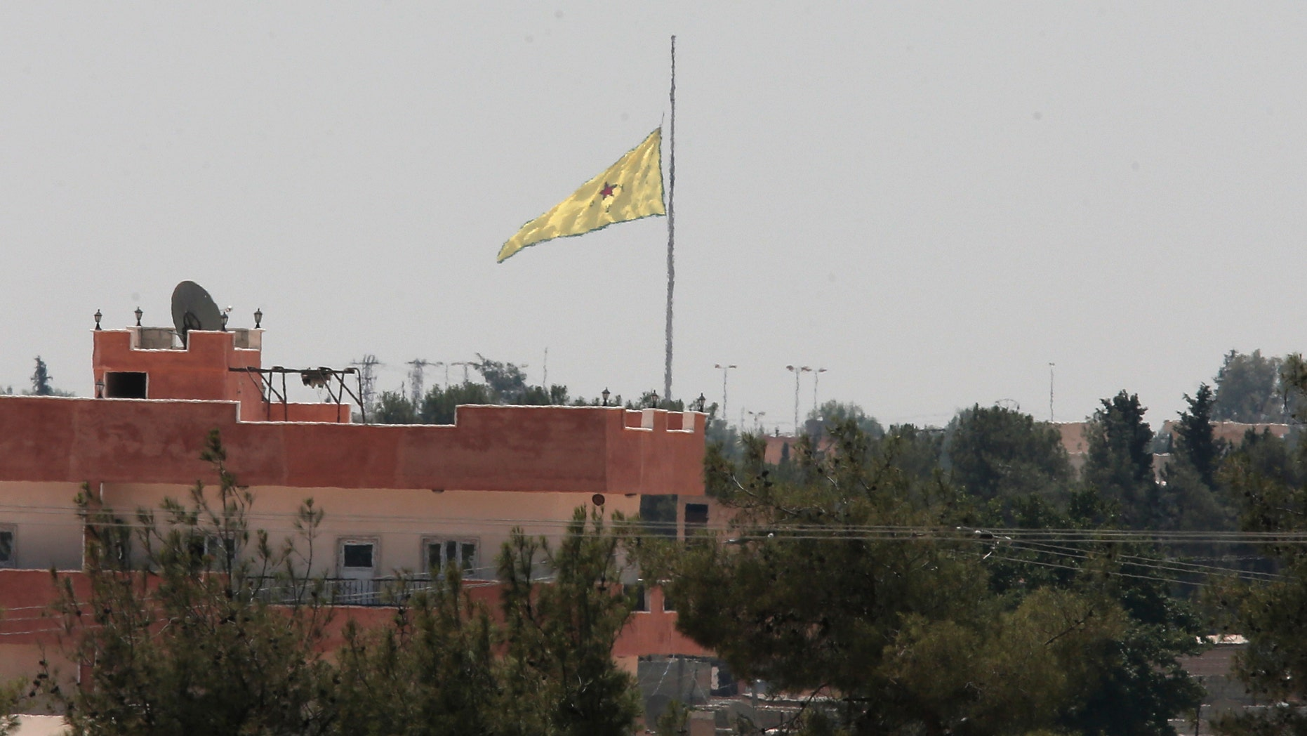 June 16, 2015 - FILE photo taken from the Turkish side of the border between Turkey and Syria, in Akcakale, southeastern Turkey. A flag of the Kurdish People's Protection Units, or YPG, flies over the town of Tal Abyad, Syria. Kurdish forces discovered a long tunnel dug by ISIS fighters near the Turkish border with Syria, a spokesman said Monday.