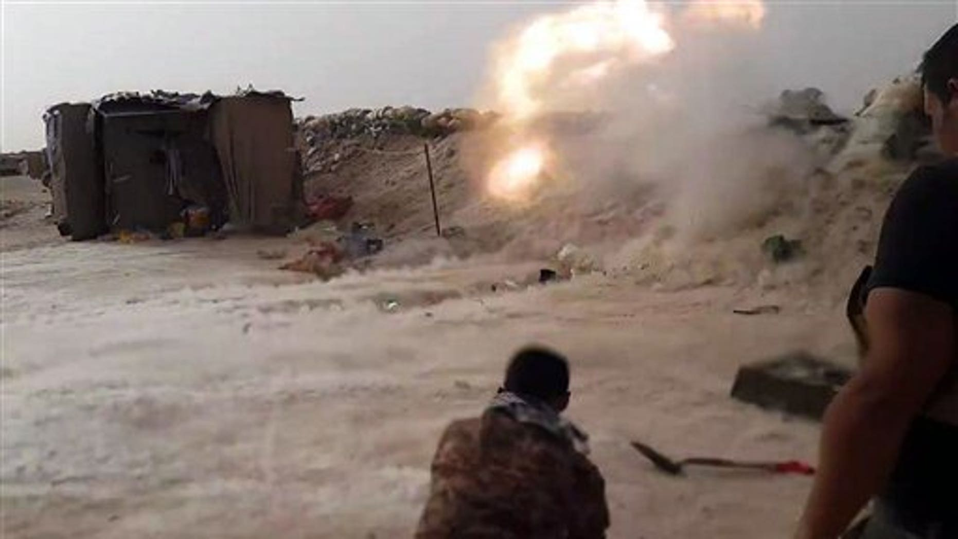 In this image taken Friday, May 29, 2015, Iraqi anti-terrorism forces battle with Islamic State group extremists as they defend their base against attack outside Fallujah, 40 miles (65 kilometers) west of Baghdad, Iraq. (AP Photo)