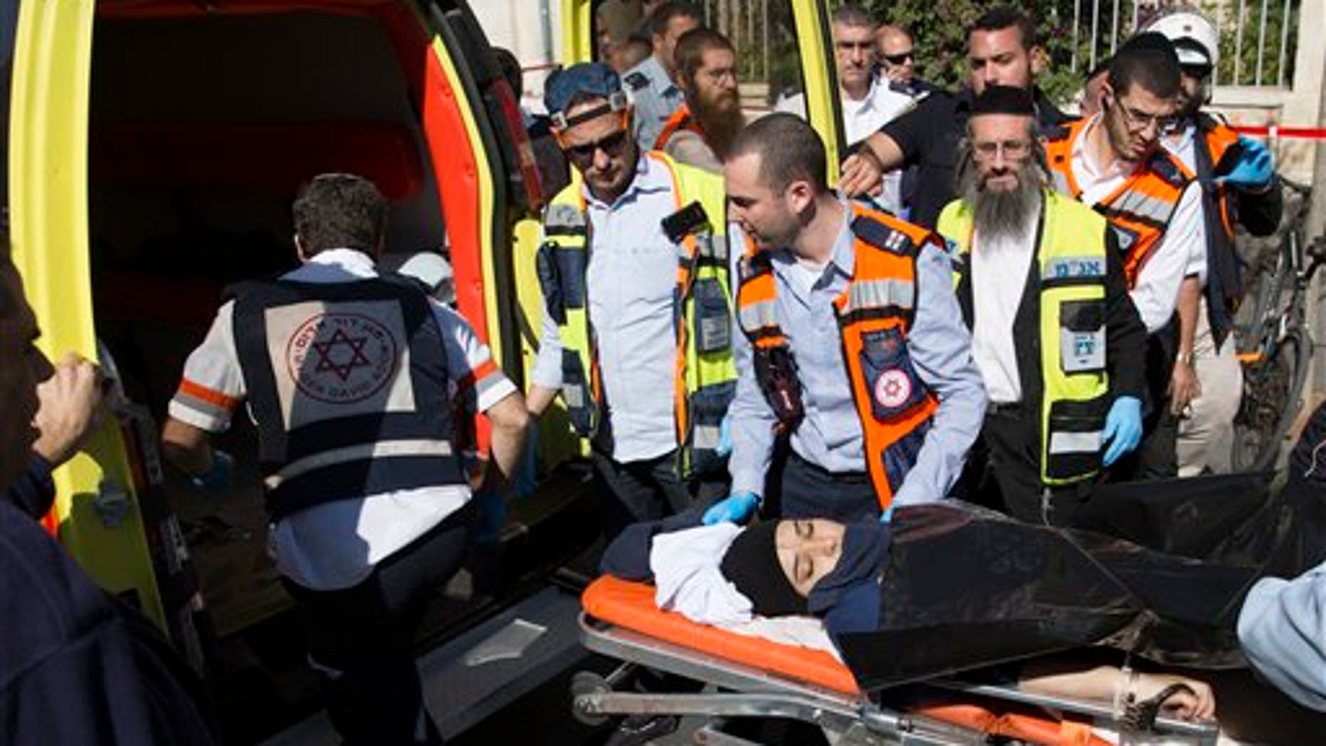 Israeli medics move a handcuffed Palestinian woman, who police believe attacked a man, at the scene of a stabbing attack in Jerusalem, Monday, Nov. 23, 2015. (AP Photo/Sebastian Scheiner)