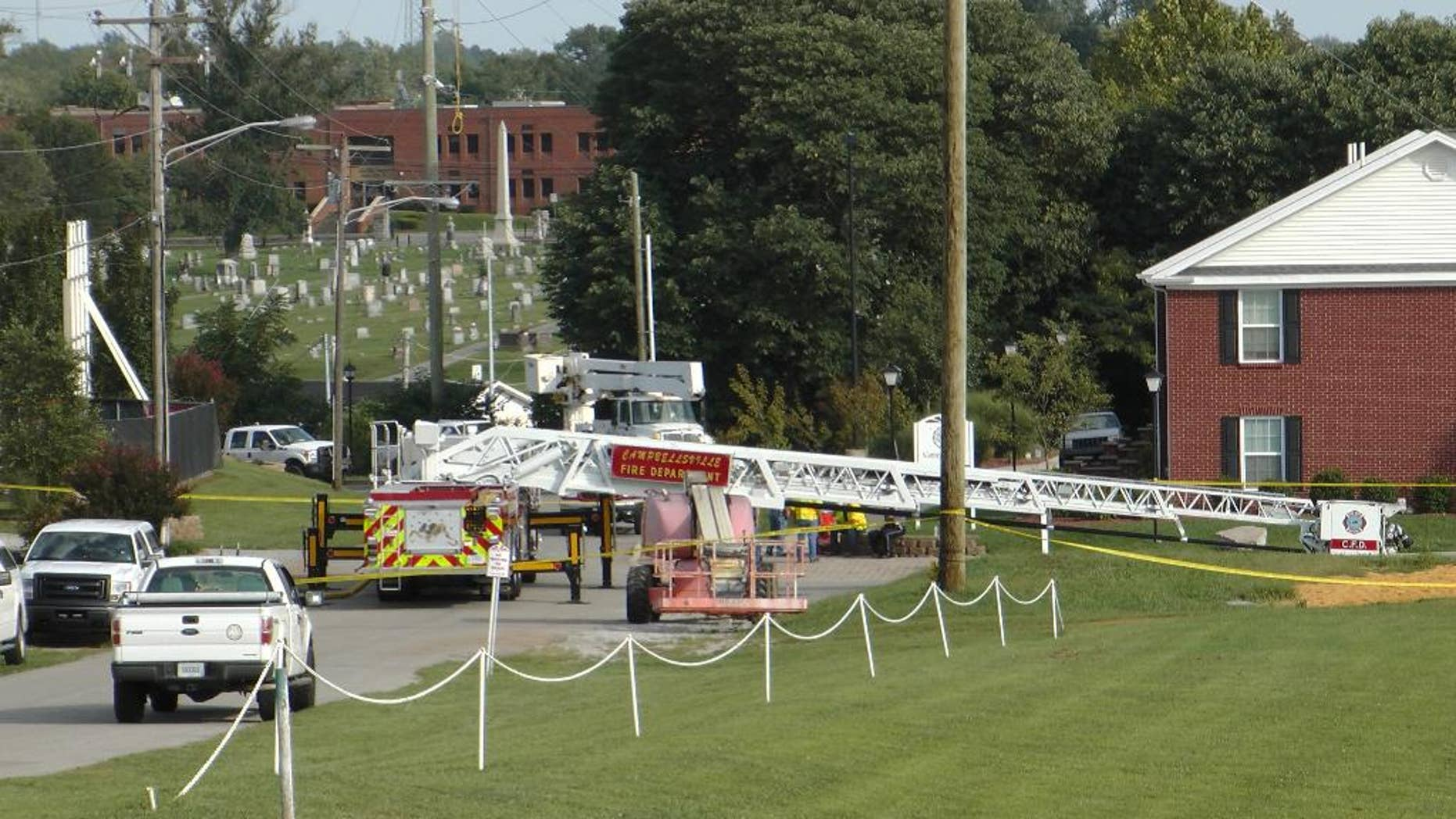 A Campbellsville Fire Department truck with the ladder extended remained at the scene where two firefighters were injured during an ice bucket challenge during a fundraiser for ALS on Thursday, Aug. 21, 2014, in Campbellsville, Ky. Officials say the ladder got too close to a power line and electricity traveled to the ladder, electrocuting the firefighters. (AP Photo/Dylan Lovan)