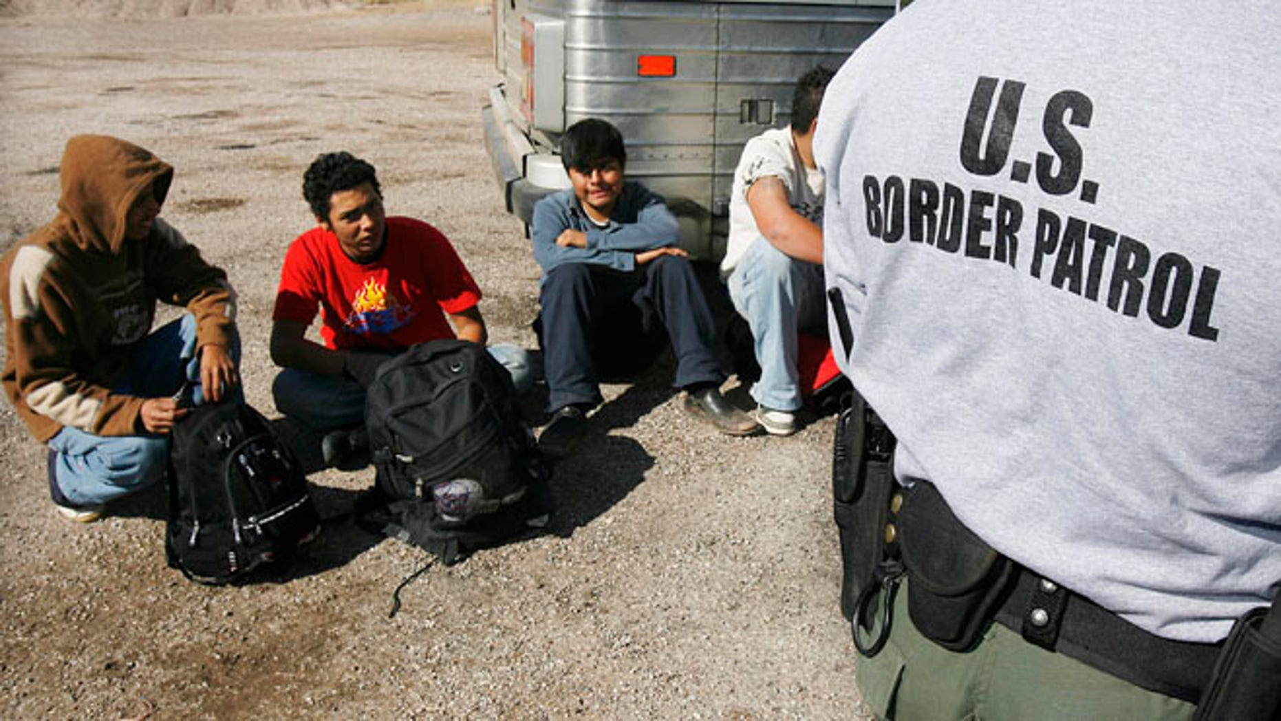 Jan. 19, 2007 file photo, the U.S. Border Patrol detains a large group of suspected immigrants at the Arizona-Mexico border in Sasabe, Ariz.