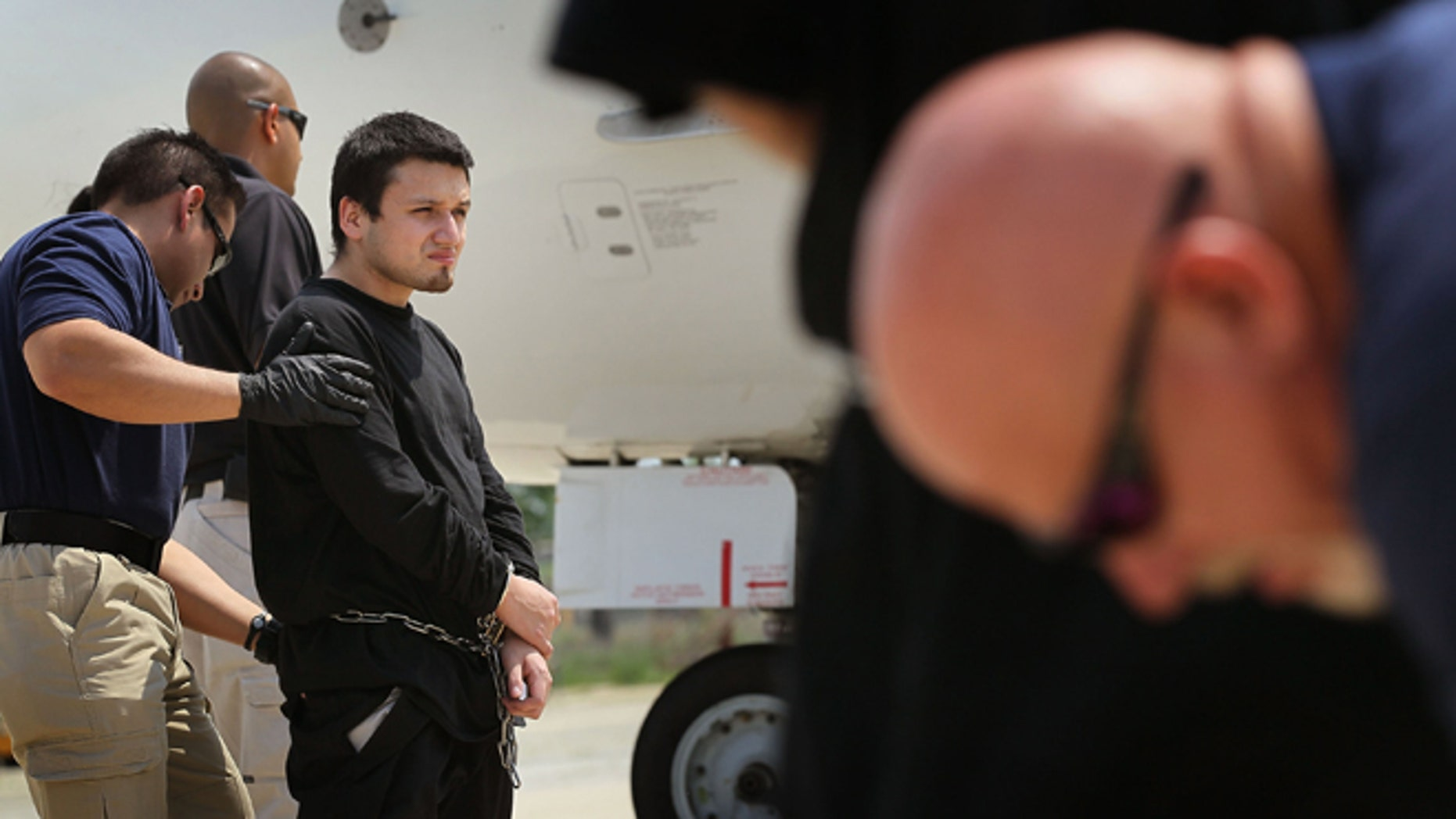 CHICAGO - MAY 25:  Ulises Hernandez is searched while being transferred from a van to a jet chartered by U.S. Immigration and Customs Enforcement (ICE) on May 25, 2010 in Chicago, Illinois. Hernandez and the other passengers on the deportation flight began the morning at an ICE processing center in suburban Chicago before boarding the flight to Harlingen, Texas where they were then bussed to Brownsville and finally walked to the Mexican border and released from custody. The U.S. deports over 350,000 immigrants a year for entering the country illegally, most are Mexican, and more than 90 percent are men.  (Photo by Scott Olson/Getty Images)