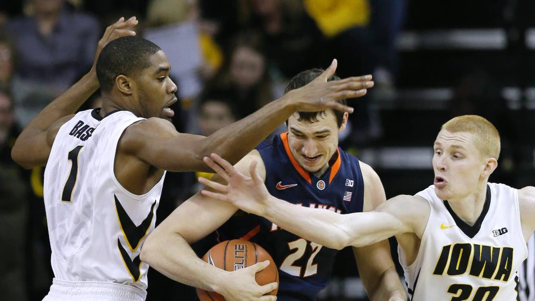 Illinois center Maverick Morgan, center, looks to drive between Iowa's Melsahn Basabe, left, and Aaron White, right, during the first half of an NCAA college basketball game on Saturday, March 8, 2014, in Iowa City, Iowa. (AP Photo/Charlie Neibergall)