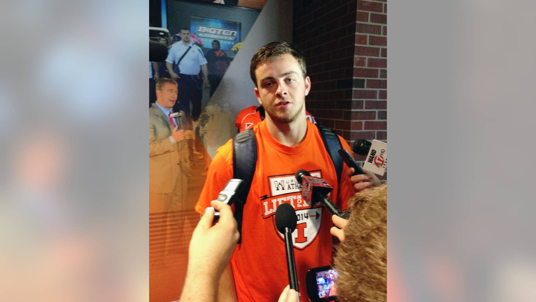 Illinois quarterback Wes Lunt talks with reporters at Memorial Stadium in Champaign, Ill., on Wednesday, Aug. 20, 2014, after learning he will be the starting Illini quarterback. Lunt transferred from Oklahoma State after starting as a freshman but sat out last season under NCAA transfer rules. Illinois starts its season Aug. 30 against Youngstown State. (AP Photo/David Mercer)