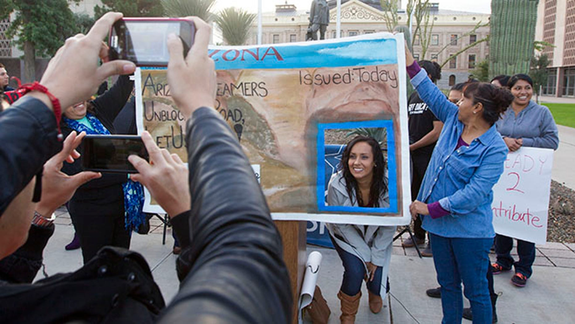 FILE - In this Dec 17, 2014, file photo, Erika Andiola gets her photo taken at the Arizona State Capitol in Phoenix, as thousands of young immigrants moved a step closer to getting driver's licenses in Arizona. A single mother battling cancer and a victim of domestic abuse are among the immigrants who qualify for Arizona driver's licenses but have been illegally denied the chance to drive a car, a group of advocacy organizations said in a new federal lawsuit. Denying licenses to some immigrants in the country illegally who have been granted deferred action, or protection from deportation, is unconstitutional, according to the claim filed Monday, Sept. 12, 2016 by the Mexican American Legal Defense and Educational Fund, the National Immigration Law Center and the Ortega Law Firm.(Nick Oza  /The Arizona Republic via AP, File)