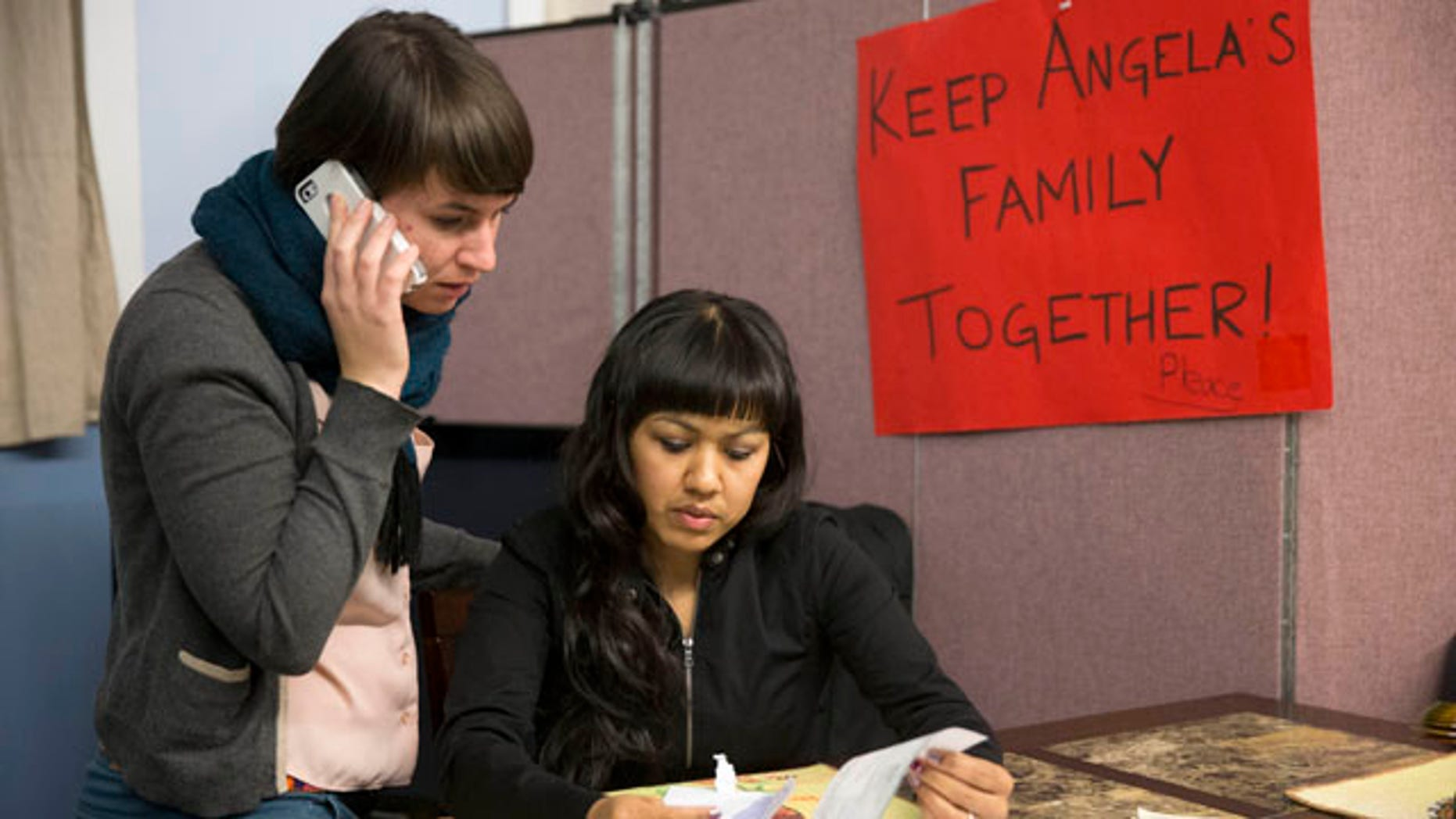 Dec. 8, 2014: Angela Navarro, right, who has been living in the U.S. with her American-born children despite a deportation order issued 10 years ago looks over a letter with New Sanctuary Movement community organizer Nicole Kligerman at the West Kensington Ministry church in Philadelphia. (AP Photo/Matt Rourke)