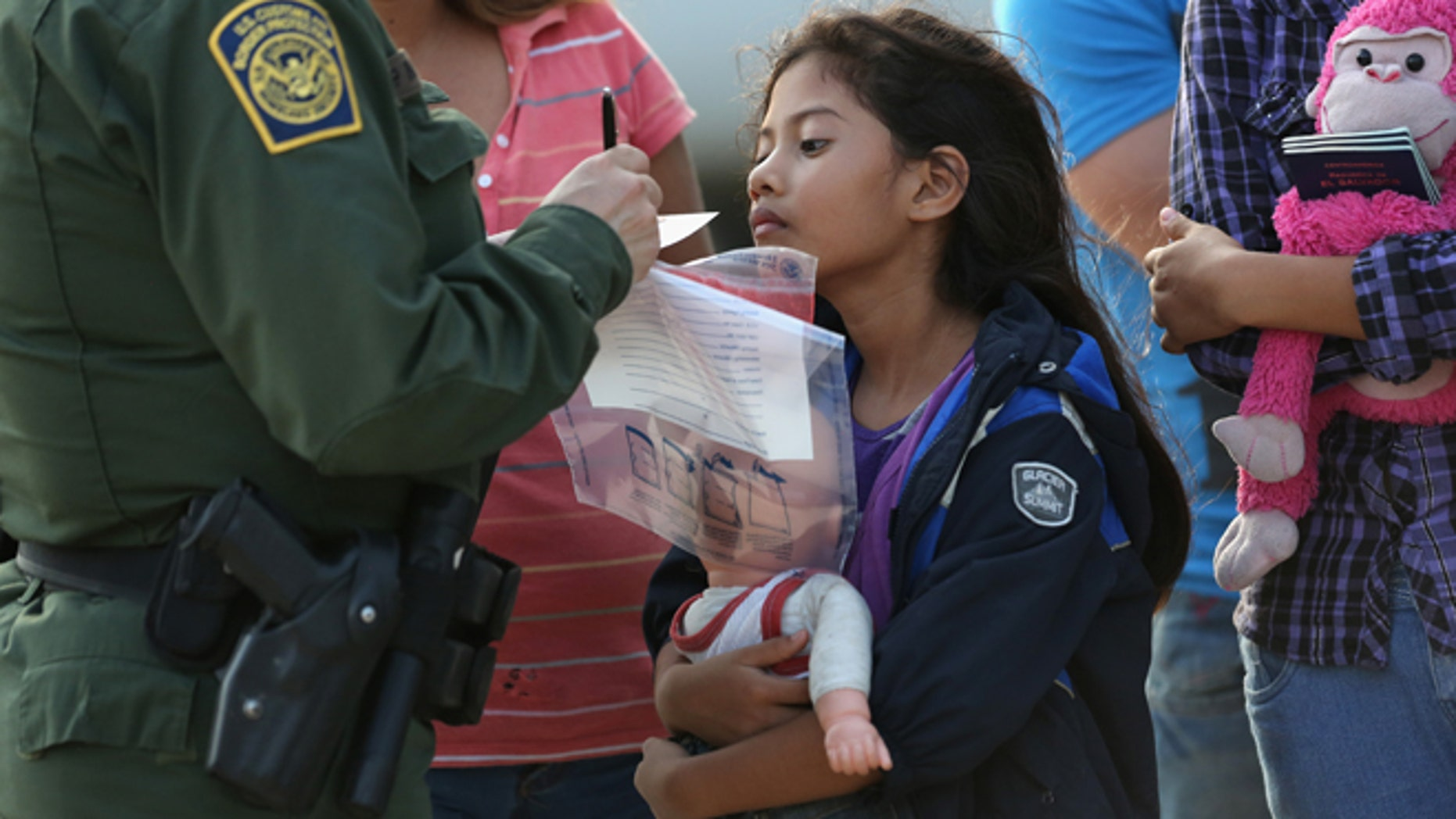 MISSION, TX - JULY 24:  Salvadorian immigrant Stefany Marjorie, 8, watches as a U.S. Border Patrol agent records family information on July 24, 2014 in Mission, Texas. Like most of the recent surge of Central American immigrant women and children, her family brought documents, often birth certificates, to prove their nationality to U.S. Border officials. Tens of thousands of immigrant families and unaccompanied minors from Central America have crossed illegally into the United States this year and presented themselves to federal agents, causing a humanitarian crisis on the U.S.-Mexico border. Texas' Rio Grande Valley has become the epicenter of the latest immigrant crisis, as more of them enter illegally from Mexico into that sector than any other stretch of the America's 1,933 mile border with Mexico.  (Photo by John Moore/Getty Images)