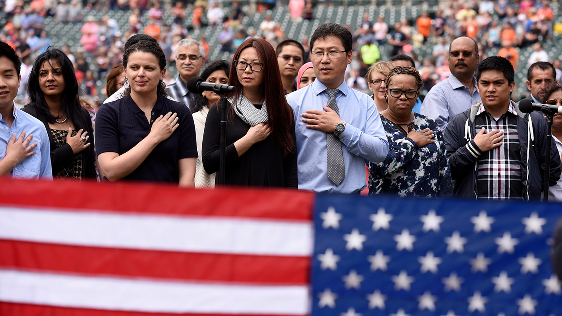 "Thirty-two Southeast Michigan immigrants recite the ""Pledge of Allegiance"" as they are sworn in to become United States citizens during a naturalization ceremony prior to a baseball game between the Detroit Tigers and the Kansas City Royals, Thursday, June 29, 2017, in Detroit. This is the 10th year the ceremony has taken place at Comerica Park during the baseball season."