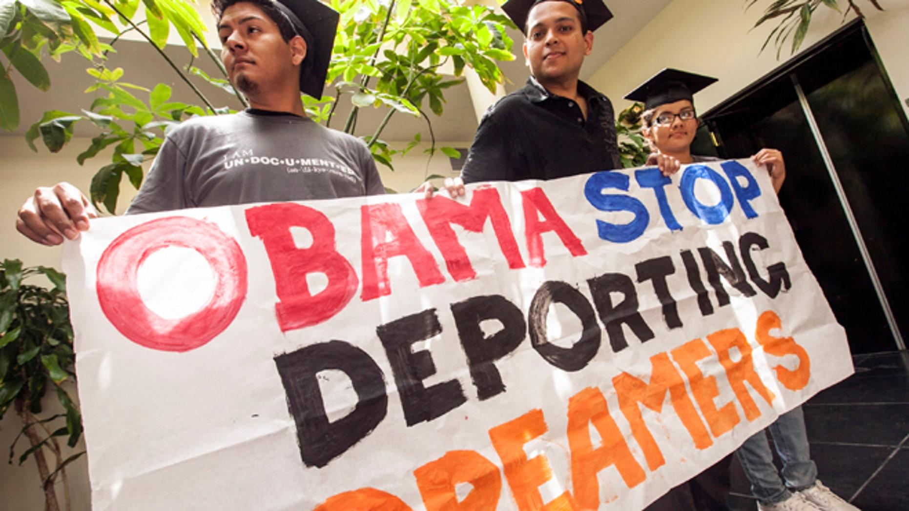 Los estudiantes David Buenrostro, Adrian James y Jahel Ramos, de izquierda a derecha, protestan fuera de las oficinas de campaña de Barack Obama en Culver City, California el jueves 14 de junio de 2012.  (AP foto/Damian Dovarganes)