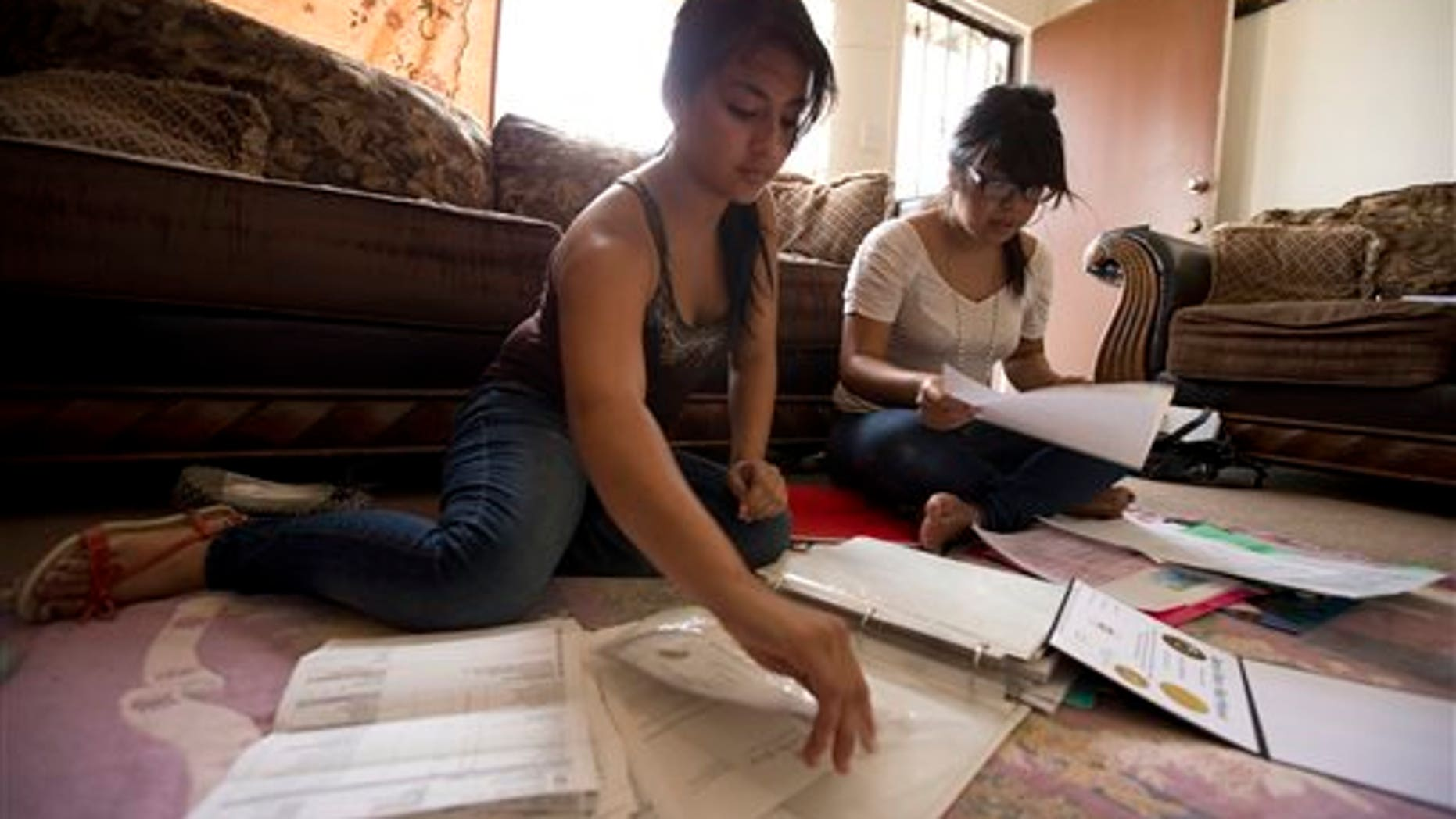 Itzel Guillen, left, sorts out some of the documents she needs to apply for a work permit along with Lucero Maganda, right, at her home  in San Diego, Ca. Guillen and Maganda are among those hoping for the right to work legally in America without being deported.(AP Photo/Gregory Bull, File)