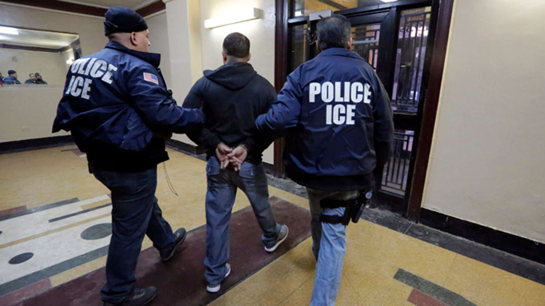 In this March 3, 2015 photo, Immigration and Customs Enforcement officers escort an arrestee in an apartment building, in the Bronx borough of New York, during a series of early-morning raids. Immigrant and Customs Enforcement say an increasing number of cities and counties across the United States are limiting cooperation with the agency and putting its officers in dangerous situations as they track down foreign-born criminals. Instead, more of its force is out on the streets, eating up resources and conducting investigations because cities like New York and states like California have passed legislation that limits many of the detention requests issued by immigration authorities.  (AP Photo/Richard Drew)