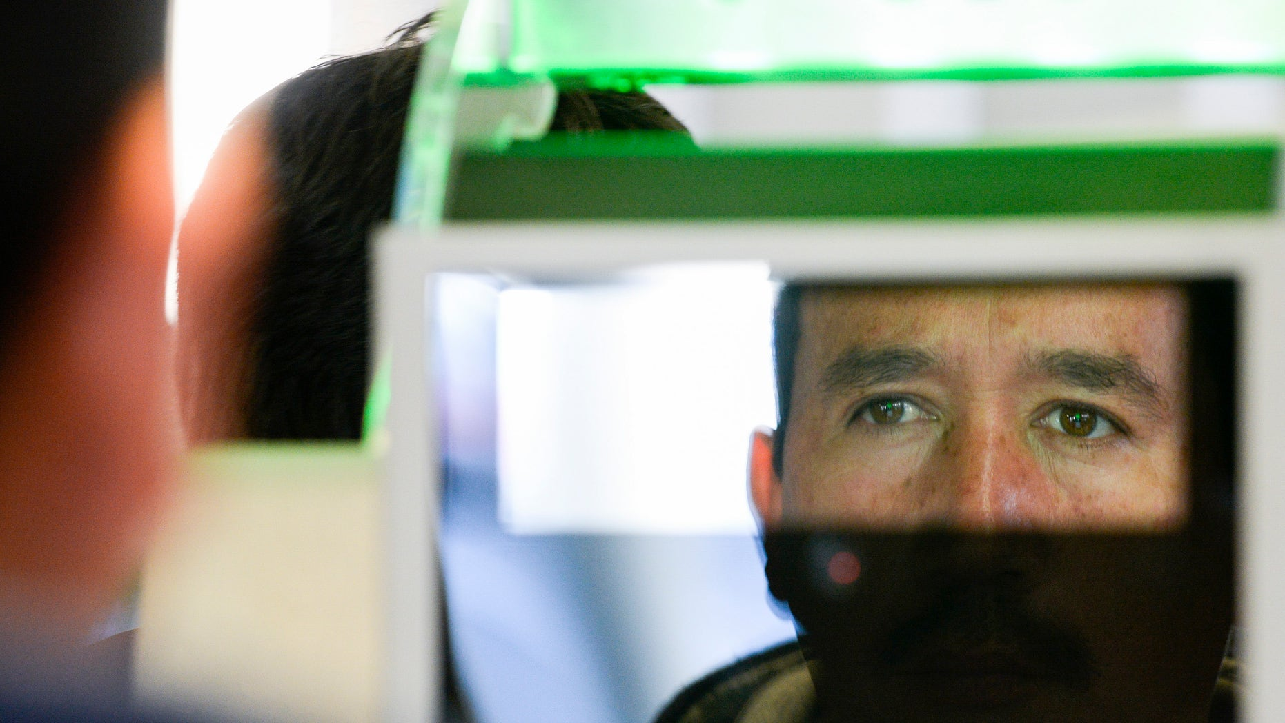 A pedestrian crossing from Mexico into the United States at the Otay Mesa Port of Entry has his facial features and eyes scanned at a biometric kiosk Thursday, Dec. 10, 2015, in San Diego.  On Thursday, U.S. Customs and Border Protection began capturing facial and eye scans of foreigners entering the country at San Diego's Otay Mesa port of entry on foot.  (AP Photo/Denis Poroy)