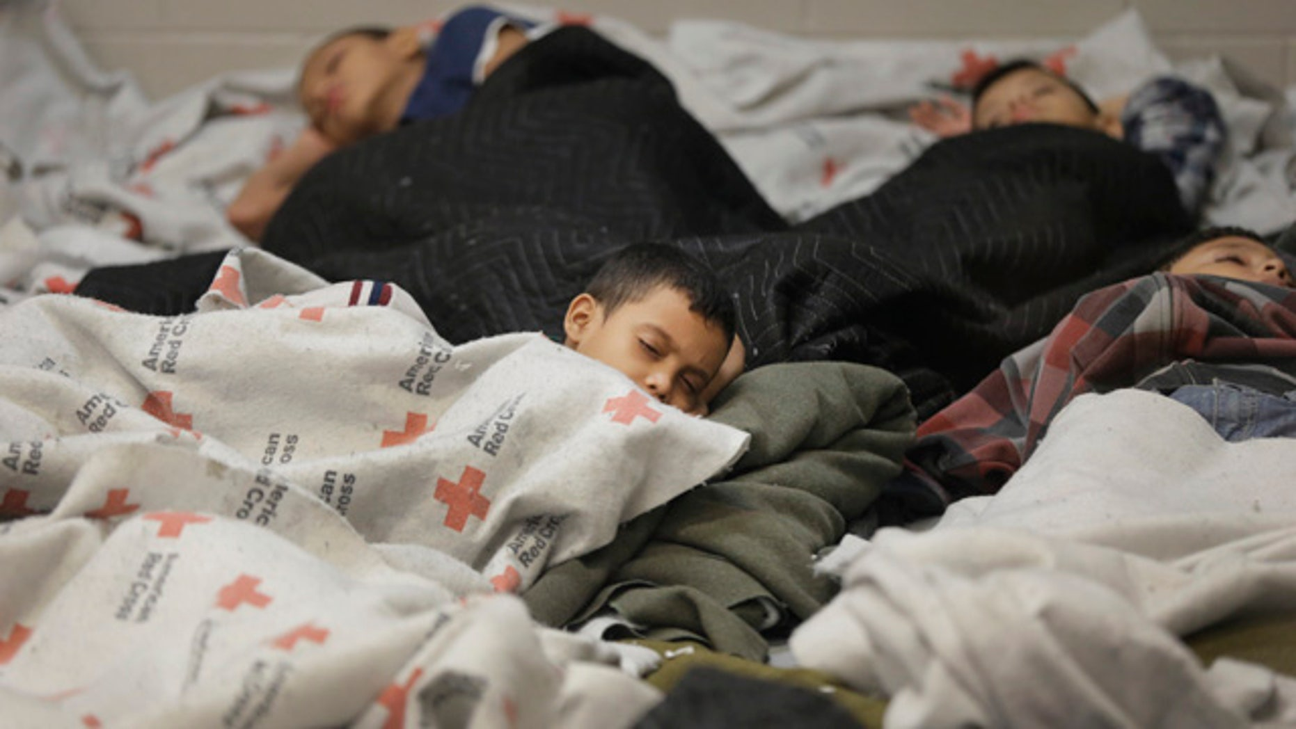 June 18, 2014: Detainees sleep in a holding cell at a U.S. Customs and Border Protection processing facility in Brownsville,Texas. (AP Photo/Eric Gay, Pool)