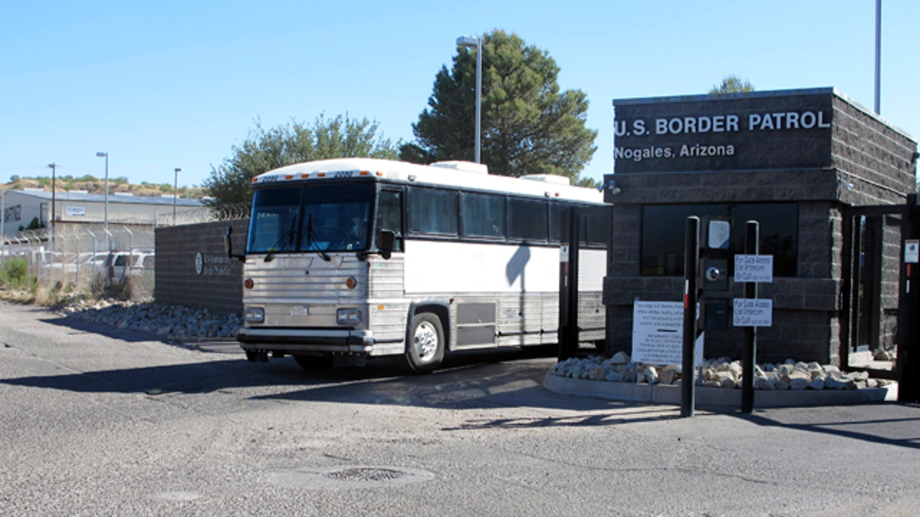 June 7, 2014: A bus leaves the entrance of the U. S. Border Patrol facility in Nogales, Ariz. Arizona officials said they are rushing federal supplies to this makeshift holding center in the southern part of the state that's housing hundreds of migrant children and is running low on the basics. (AP Photo/Brian Skoloff)