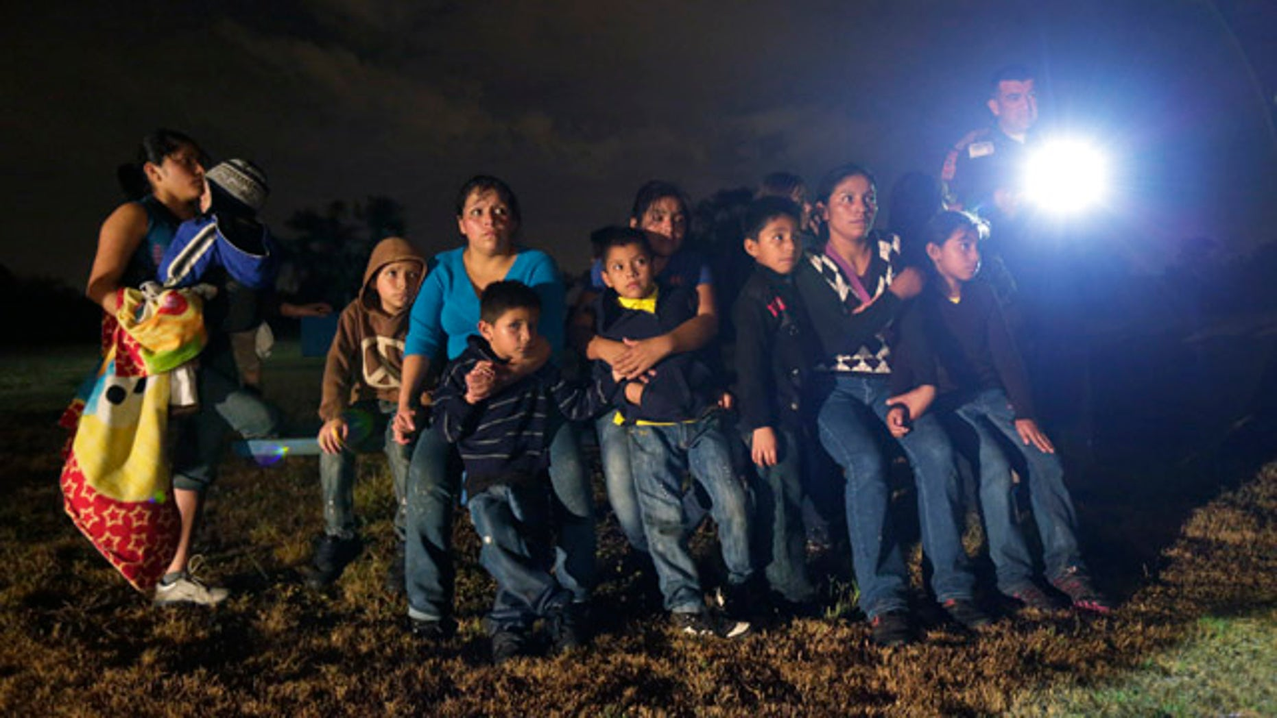 June 25, 2014: A group of immigrants from Honduras and El Salvador who crossed the U.S.-Mexico border illegally are stopped in Granjeno, Texas. (AP Photo/Eric Gay)