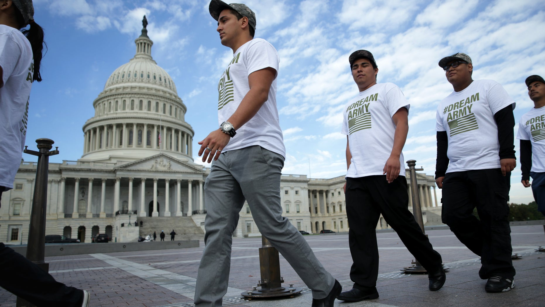 """WASHINGTON, DC - OCTOBER 23:   (L-R) Lizardo Buleje of San Antonio, Texas, Jorge Tellez of Parker, Colorado, Anthony Corona of Staten Island, New York, and Armando Jimenez of Allen Town, Pennsylvania, march in front of the U.S. Capitol during a rally on immigration reform October 23, 2013 on Capitol Hill in Washington, DC. The Dream Action Coalition held a rally and briefing to discuss """"how the outdated immigration system undermines military readiness, separates military families, and prevents talent from joining its enlisted and officer ranks."""" (Photo by Alex Wong/Getty Images)"""