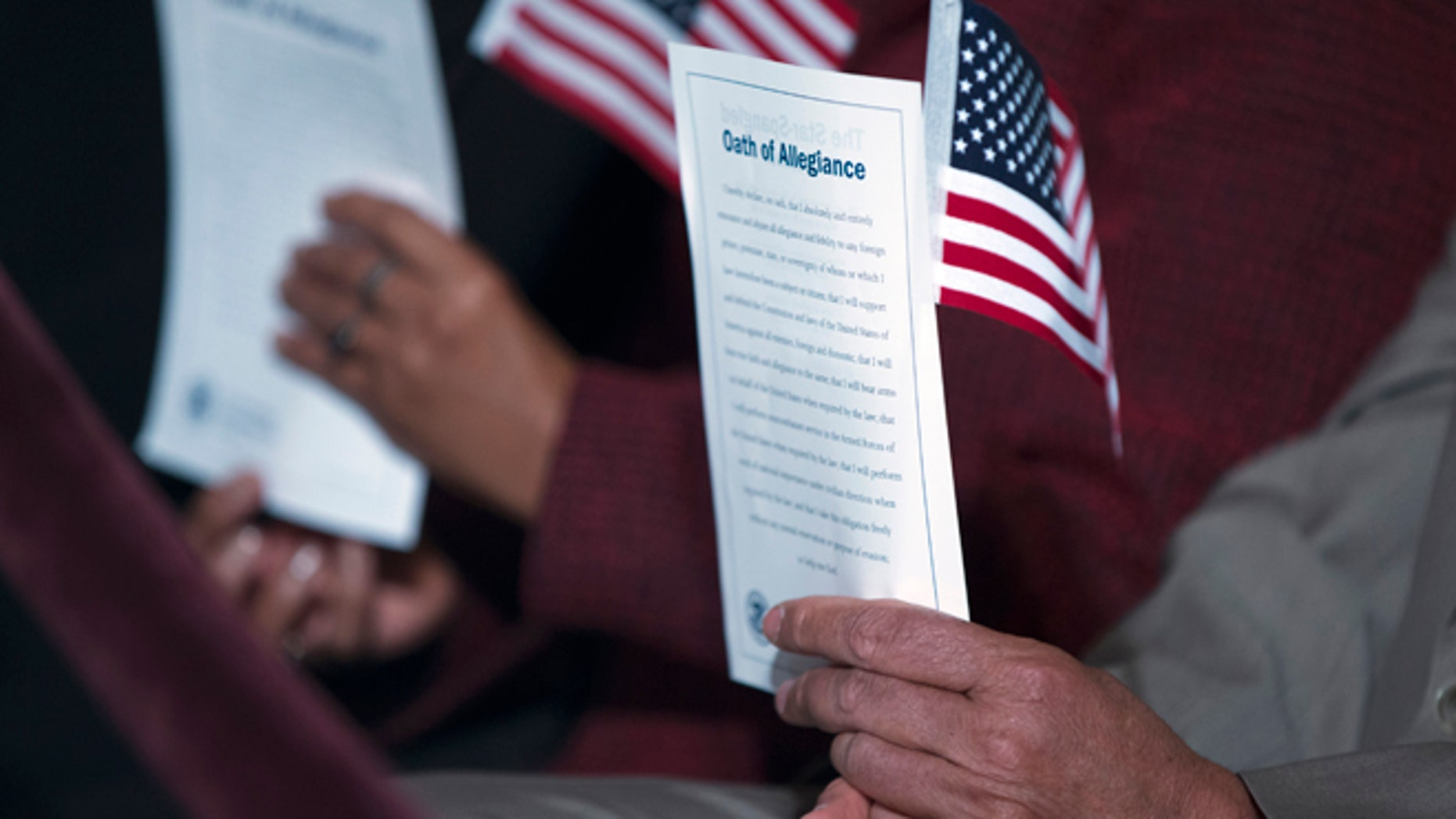 """In this Dec. 15, 2015, photo, participants hold the """"Oath of Allegiance"""" and American flags during a naturalization ceremony attended by President Barack Obama at the National Archives in Washington. More Americans favor than oppose a pathway to citizenship for immigrants who are living in the United States illegally, a new Associated Press-GfK poll shows. While most Republicans oppose such a path to citizenship, it doesn't seem to be a dealbreaker issue for them.  (AP Photo/Evan Vucci)"""