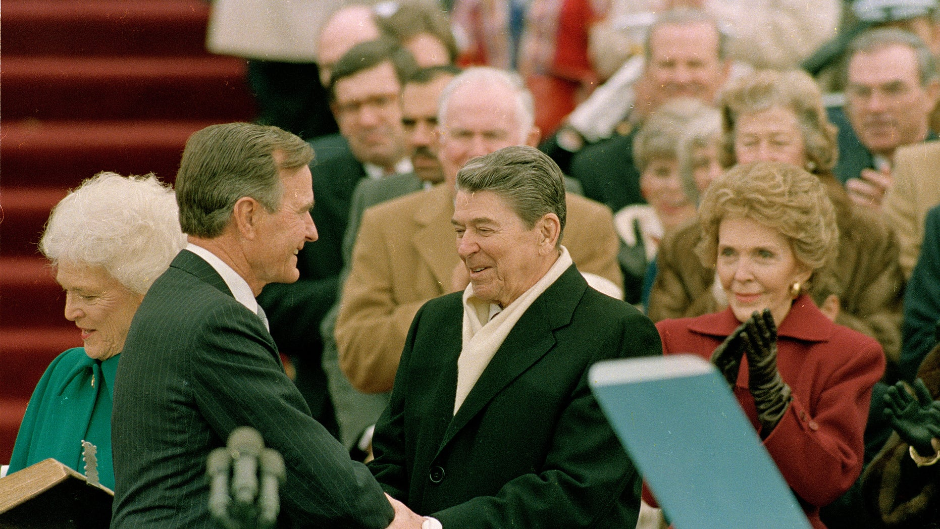 FILE - In this Jan. 20, 1989, photo, President George H.W. Bush, left, is congratulated by outgoing President Ronald Reagan after Bush took the oath of office as the 41st president of the United States on Capitol Hill in Washington. The inauguration of the U.S. president is traditionally a highly-scripted celebration, with seating charts, schedules, dress rehearsals, and planning committees that map each moment of the history-making day from start to finish. But sometimes the unexpected happens. Bush was inaugurated on the 200th anniversary of the presidency, and so one of the two Bibles on which he rested his hand during the oath of office was the same Bible that George Washington used in 1789. The other Bible belonged to the Bush family. The day also marked the first friendly transition in 60 years. (AP Photo/Bob Daugherty)