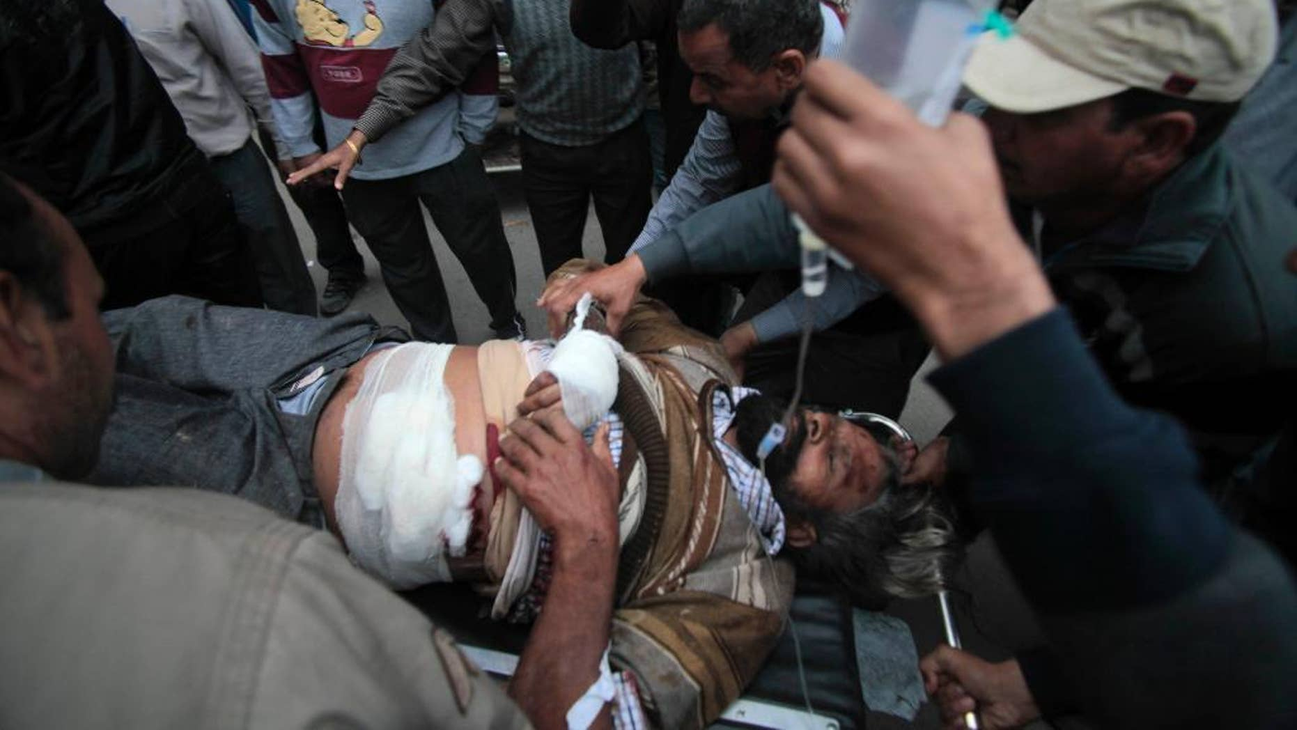 An injured man is carried on a stretcher for treatment to the Government Medical College after an attack in Jammu, India, Friday, March 28, 2014. One person was killed and three others injured Friday when unidentified gunmen wearing army uniform stopped a vehicle on the Jammu-Pathankot National Highway and shot its occupants, police said. The gunmen later escaped in the same vehicle. (AP Photo/Channi Anand)