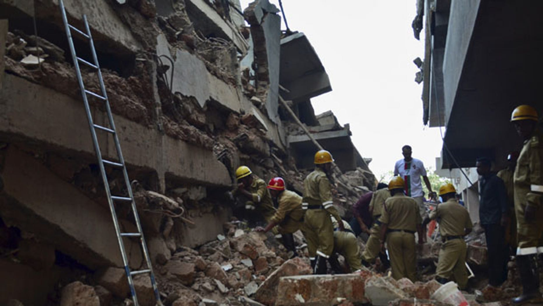 January 4, 2014: Rescue workers stand amid the debris of a building that collapsed in Canacona, a city about 44 miles from the state capital of Panaji, India. (AP Photo)