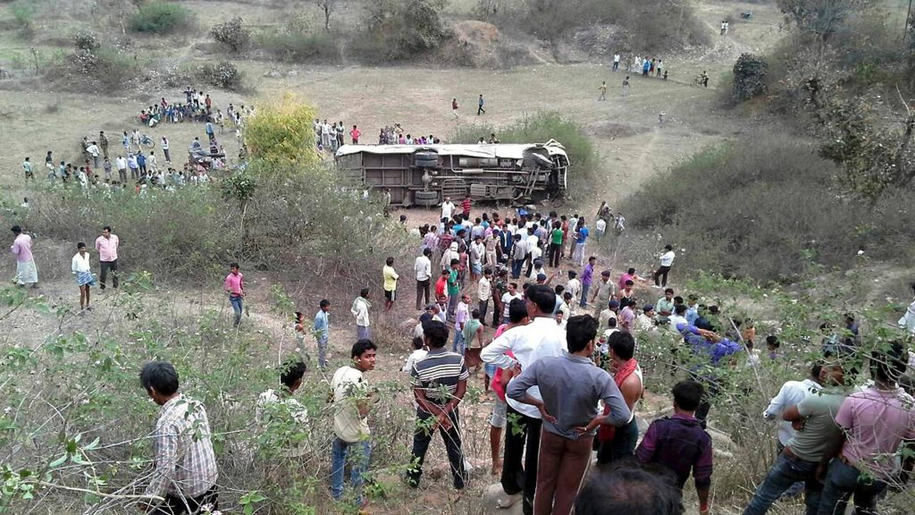 Indians gather near a passenger bus that overturned after it plunged into a gorge, in Garhwa district of Jharkhand state, India, Monday, March 30, 2015. The accident happened after the bus driver lost control of his vehicle on a sharp curve on a mountain road. The bus was traveling from Raipur city to the neighboring state of Bihar when the accident occurred.(AP Photo)