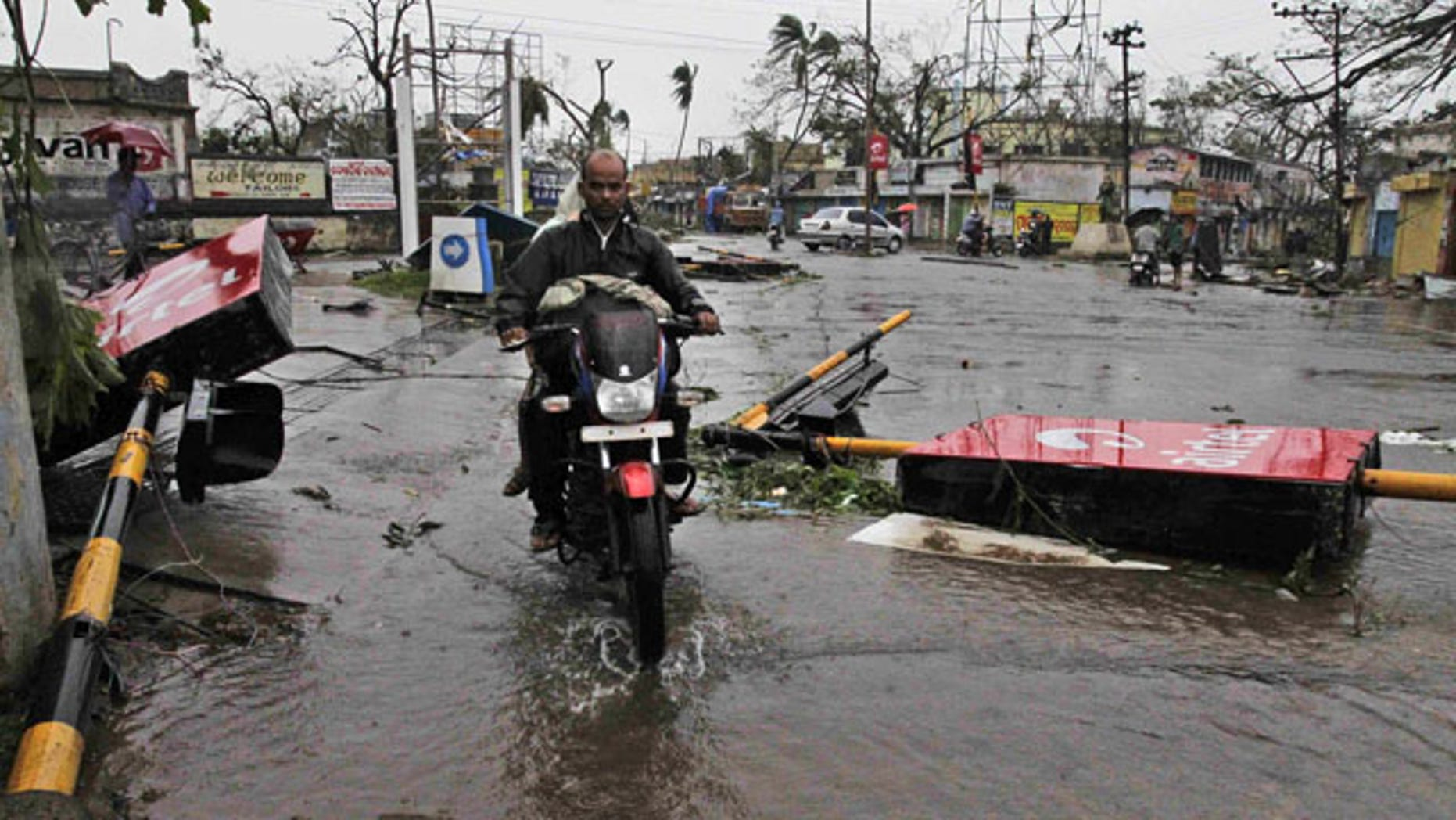 October, 13: 2013: A motorcyclist rides past fallen traffic signal poles during Cyclone Phailin at a road crossing in Berhampur, India Sunday.