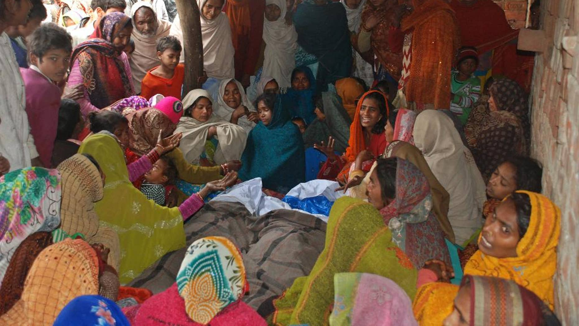 Indian women mourn around the bodies of two men, who died after consuming a bad batch of bootleg liquor in Datli village, about 30 kilometers (almost 20 miles) southwest of Lucknow, India, Tuesday, Jan. 13, 2015. More than 25 people were killed and at least 160 others hospitalized, officials said Tuesday. Many of the victims were among more than 200 people who had gathered to watch a cricket match Sunday evening in the village. (AP Photo/Sanjay Sonkar)