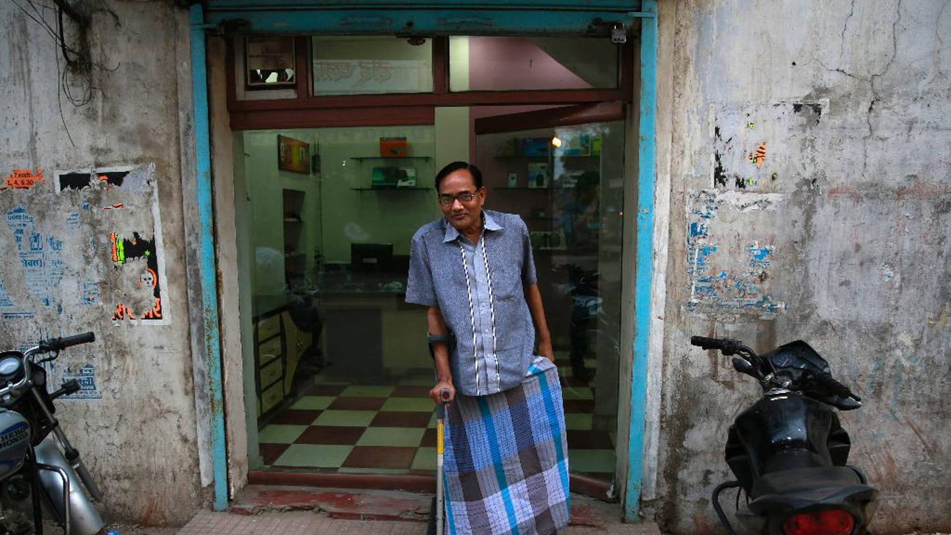 In this April 15, 2014 photo, India's Ramesh Agrawal walks outside his shop during an interview in Raigarh in Chhattisgarh state, India. Six environmental advocates from India, Peru, Russia and three other nations have won this year's Goldman Prize, which is awarded annually for grass-roots activism. Agrawal received the prize for helping villagers fight a large coal mine in Chhattisgarh state, the San Francisco-based Goldman Environmental Foundation said Monday. (AP Photo/Rafiq Maqbool)
