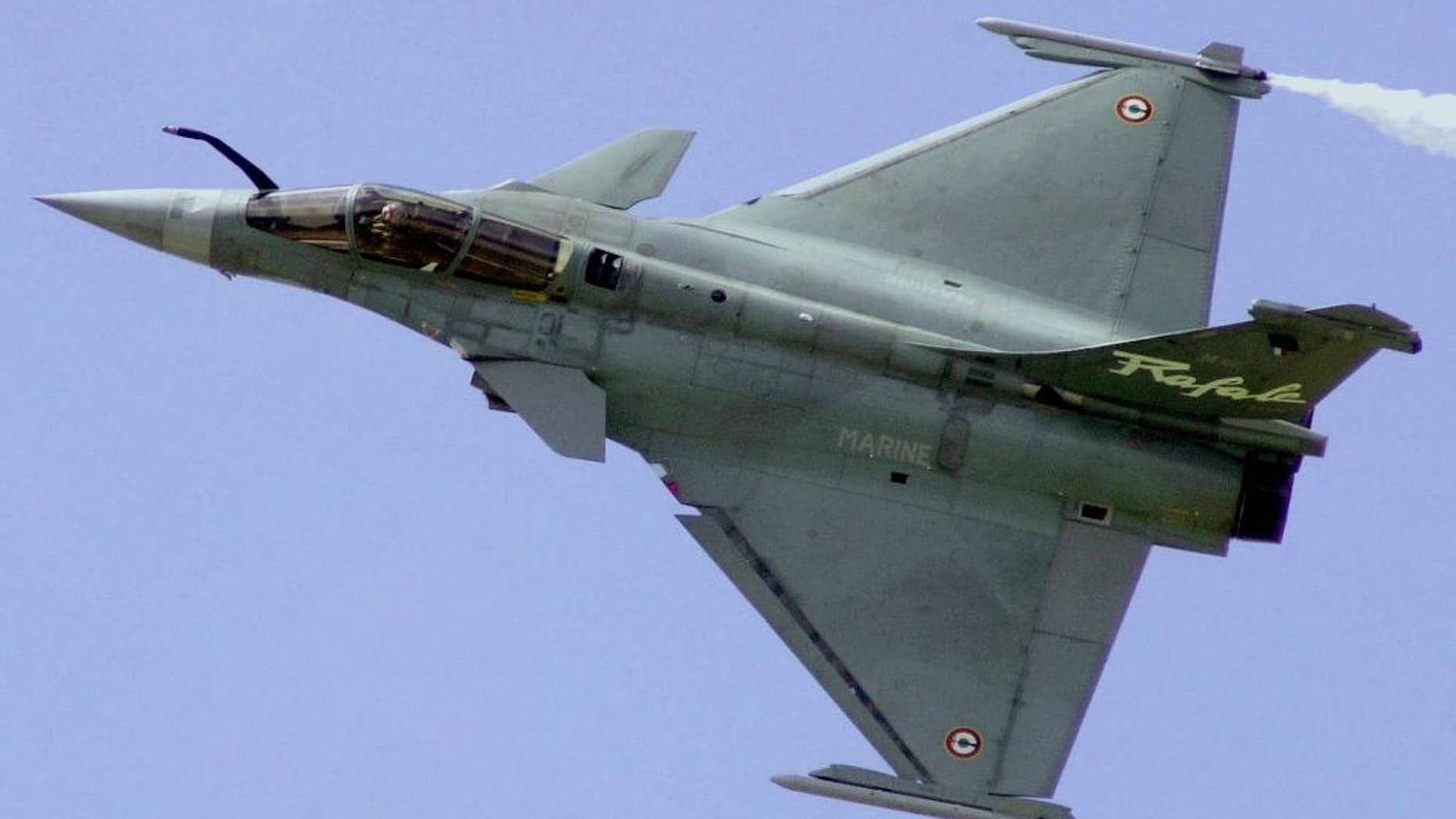 FILE - In this June 21, 2001 file photo, a French Air Force Rafale manufactured by France's Dassault Aviation speeds above Le Bourget airport, north of Paris, during the 44th Paris Air Show, in France. A French defense official said Tuesday, Dec. 2, 2014, India is close to finalizing a deal to buy 126 Rafale fighter planes for about 12 billion euros ($15 billion). It would mark France's first foreign sale of the combat-tested planes. (AP Photo/Remy de la Mauviniere, File)