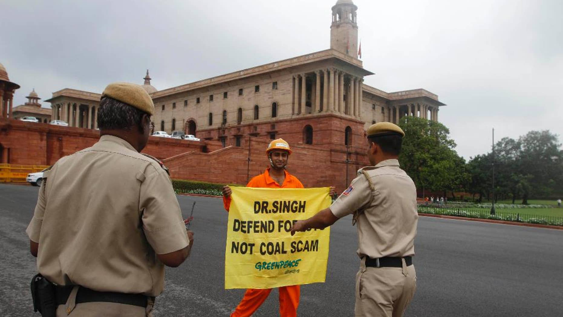 FILE- In this Aug. 21, 2012 file photo, Indian policemen prepare to remove a Greenpeace activist as he holds a banner near the area of government offices and the Indian Parliament in New Delhi, India. India's home ministry says it is temporarily suspending the registration of Greenpeace India because it is under-reporting foreign contributions and using them without government approval. (AP Photo, file)