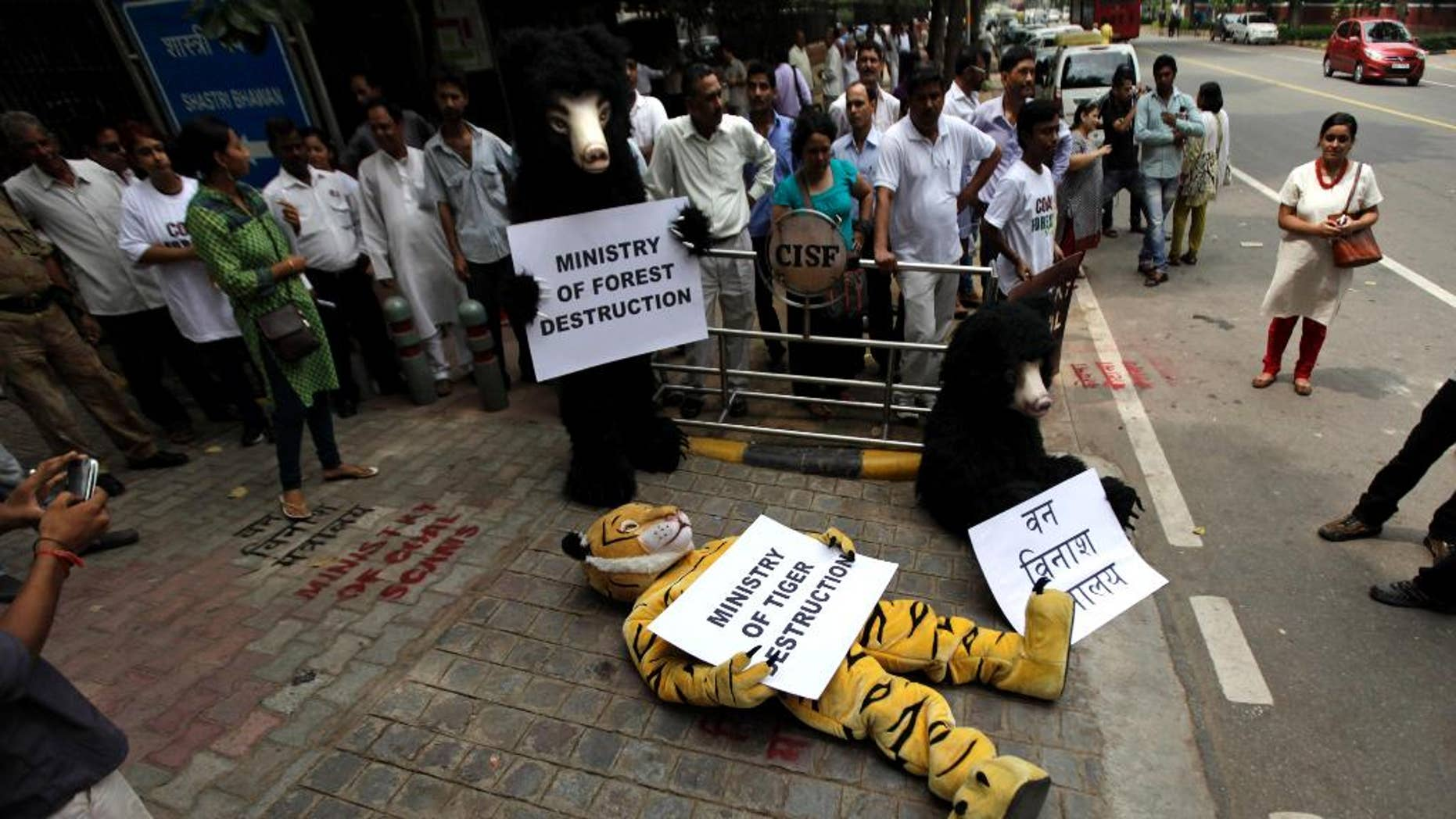 In this Tuesday, Sept. 11, 2012, file photo, Greenpeace activists dressed as wild animals hold placards during a protest outside the office of the Indian Coal Minister demanding a halt in allocation of forest land for coal mining, in New Delhi, India. A court has ordered the Indian government to release $300,000 sent by Greenpeace's foreign partners for use in India by the environmental group. (AP Photo/Altaf Qadri)