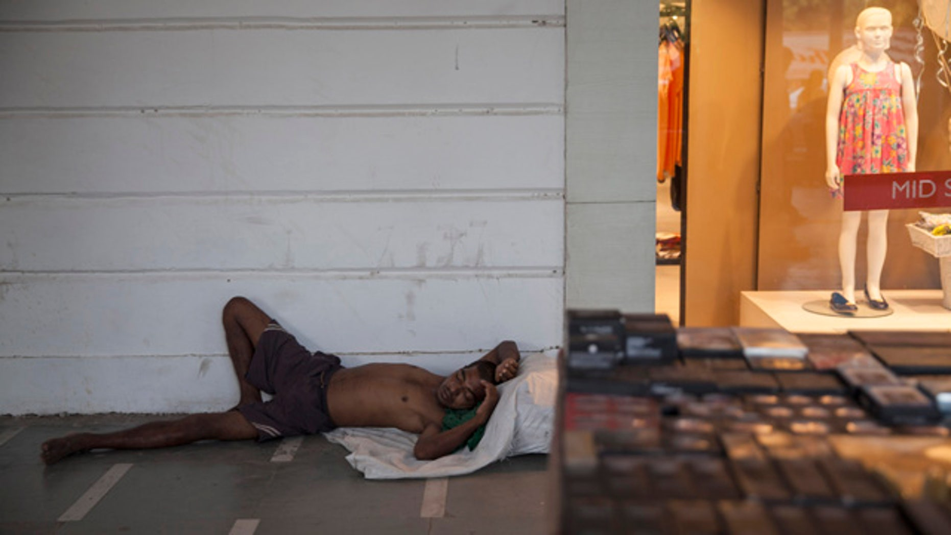 May 27, 2015: An Indian homeless man sleeps on a pavement in a market area on a hot summer day in New Delhi. In southern India, hundreds of people have died since the middle of April as soaring summer temperatures scorch the country, officials said Tuesday. (AP Photo/Tsering Topgyal)