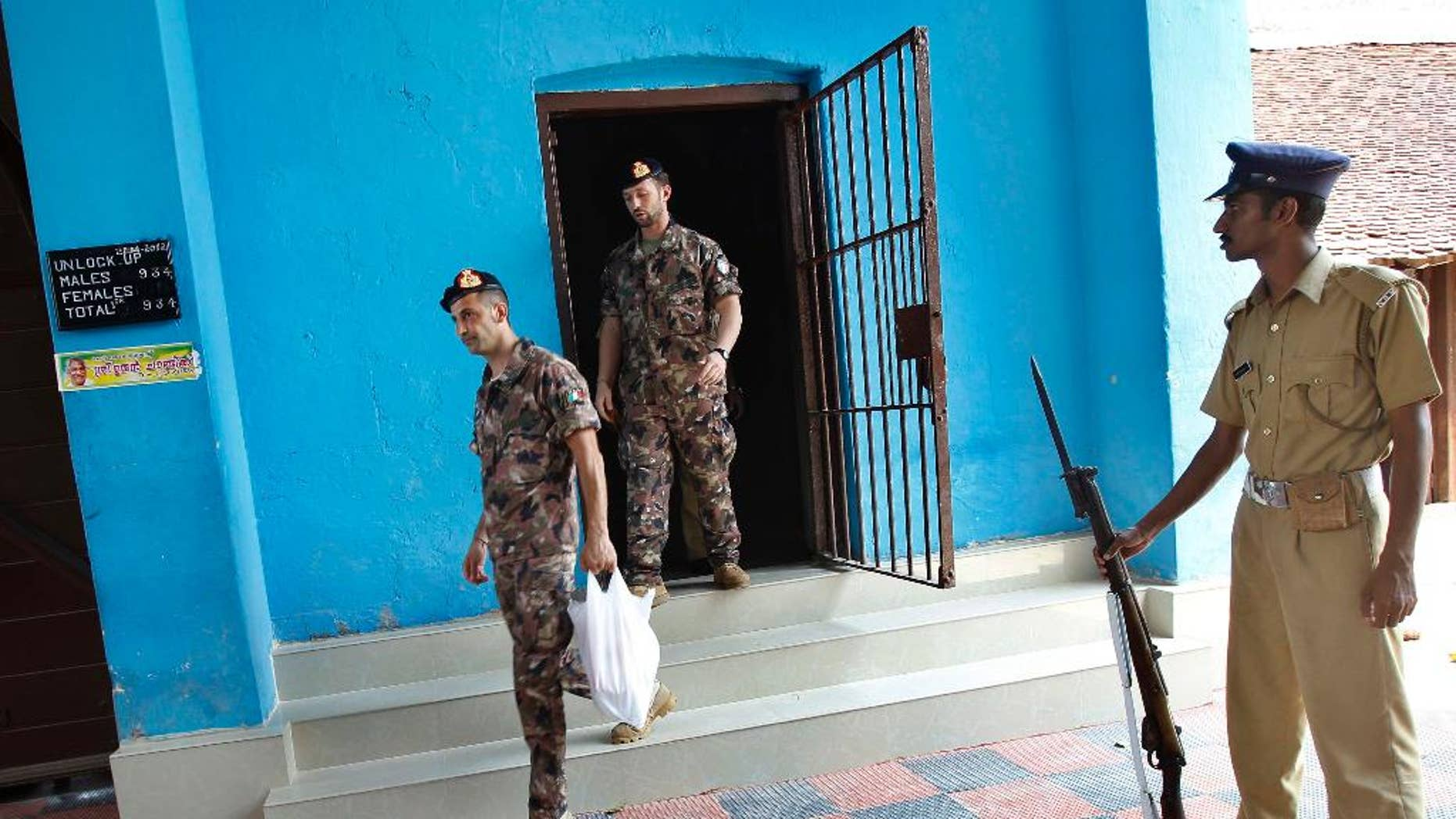FILE- In this April 22, 2012 file photo, an Indian policeman stands guard as Italian marines Massimiliano Latorre, left, and Salvatore Girone, center, walk to enter main premises of the central prison, where they were then detained in Trivandrum, India. India's top court turns down travel appeals by two Italian marines accused of killing two Indian fishermen in 2012.The Supreme Court on Tuesday, Dec.16, 2014 denied Massimiliano Latorre permission to remain in his country for two more months. (AP Photo/Aijaz Rahi, file)