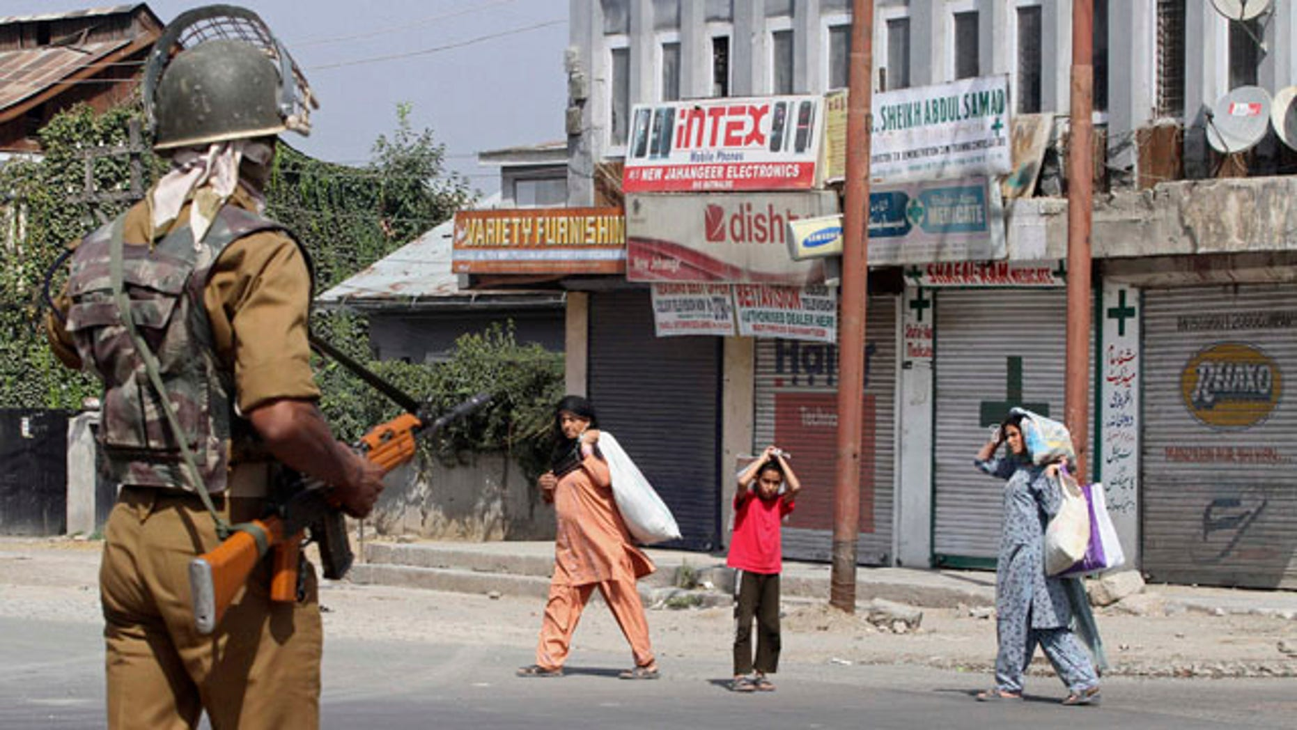 September 17: An Indian paramilitary soldier asks civilians to stay indoors during curfew in Srinagar, India.  Violent civil unrest against New Delhi's rule in Kashmir has roiled the disputed Himalayan region for the past three months and killed dozens, prompting authorities to declare curfew. (AP)