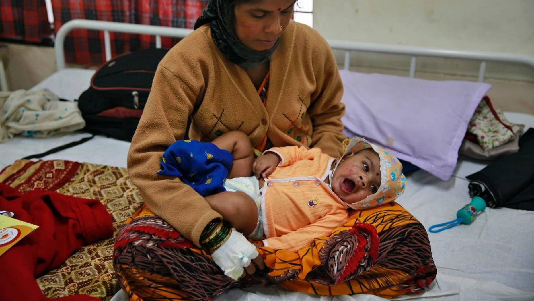 Landslide survivor Pramila Lende holds her son Rudra who was injured in the same landslide, at a hospital in Manchar, in the western Indian state of Maharashtra, India, Friday, Aug. 1, 2014. One of the few people pulled alive from the rubble in the hours after the landslide were Lende and her 3-month-old son. Lende said she was feeding her son when she heard the roar of earth and mud ripping down the hillside. Rescuers searching for dozens of people still missing after the landslide. Chances of finding anyone alive were increasingly slim. (AP Photo/Rafiq Maqbool)