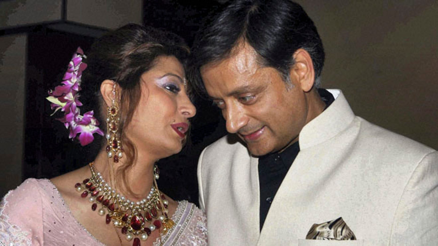 Sept. 4, 2010: In this file photo, former Indian Junior Foreign Minister Shashi Tharoor listens to his wife Sunanda Pushkar at their wedding reception in New Delhi, India.