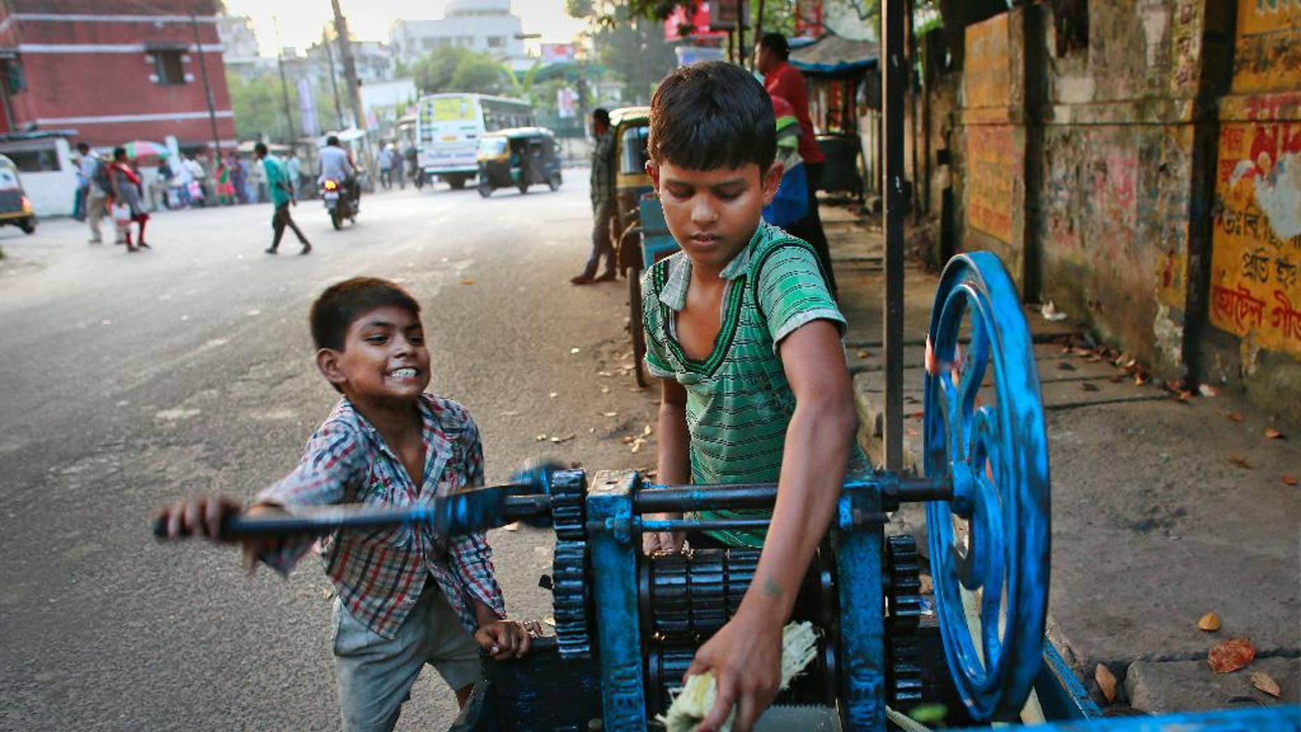 Ravi, 8, left, and Guddu, 12, extract sugarcane juice, in Gauhati, India, Friday, Oct. 10, 2014. Malala Yousafzai of Pakistan and Kailash Satyarthi of India won the Nobel Peace Prize on Friday, Oct. 10, 2014, for risking their lives to fight for children's rights. (AP Photo/Anupam Nath)