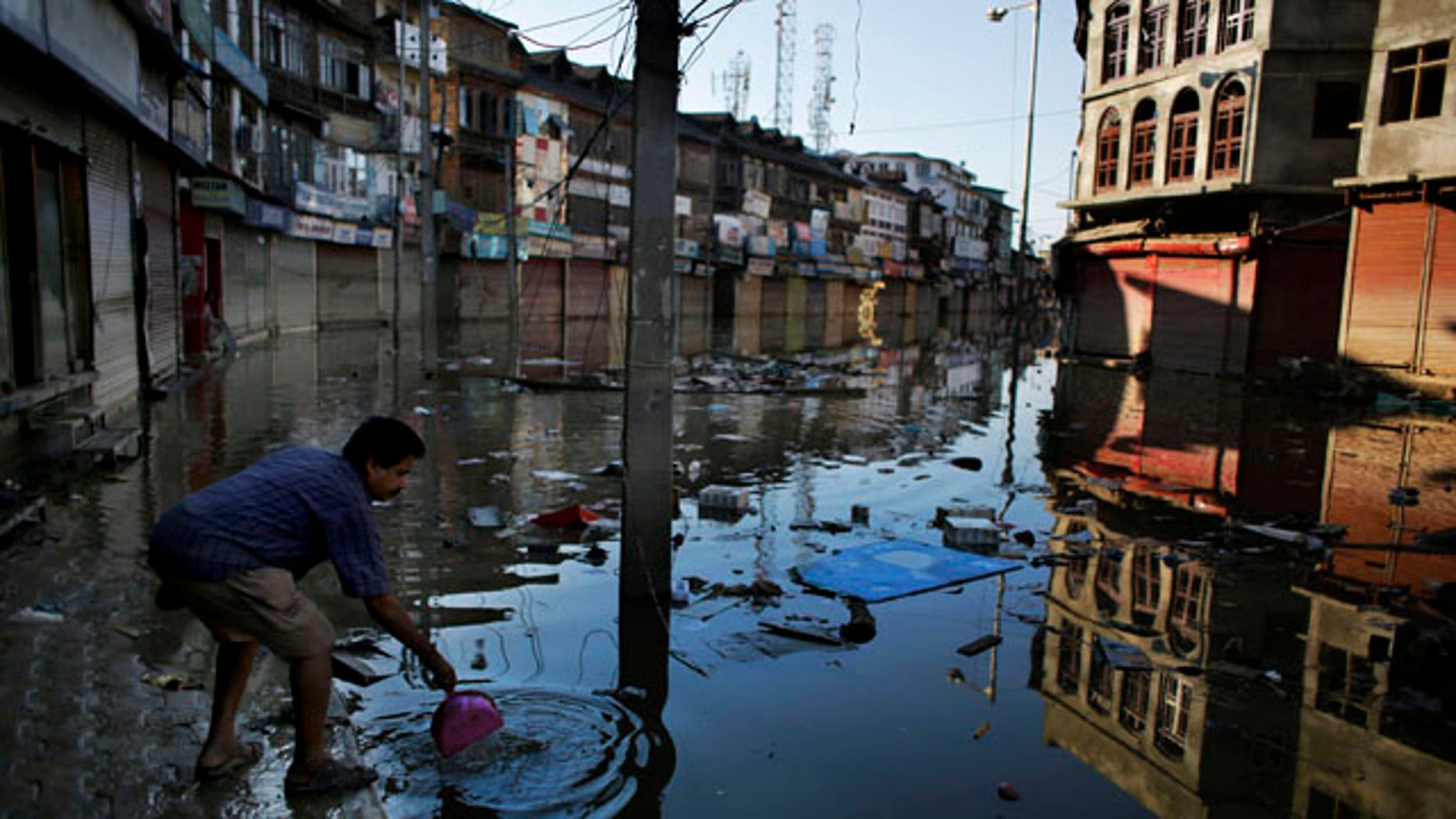 September 16, 2014: A shopkeeper throws the silt he removed from his shop into the receding flood waters in Srinagar, Indian-controlled Kashmir. (AP Photo/Altaf Qadri)