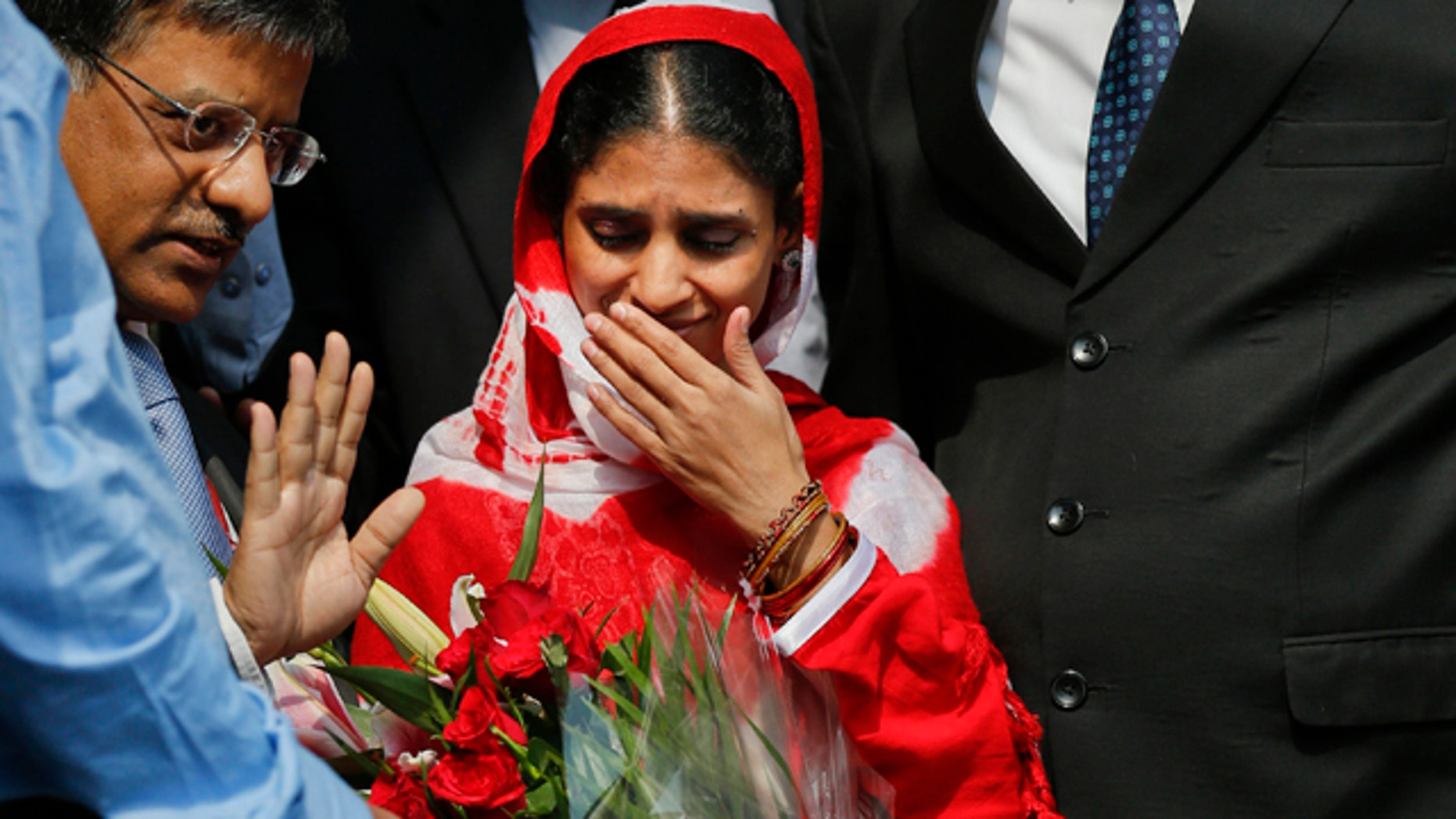 Oct. 26, 2015: Geeta, 23, center, a deaf and mute Indian woman who accidentally strayed into Pakistan as a child 12 years ago, arrives at the airport in New Delhi. (AP Photo /Tsering Topgyal)